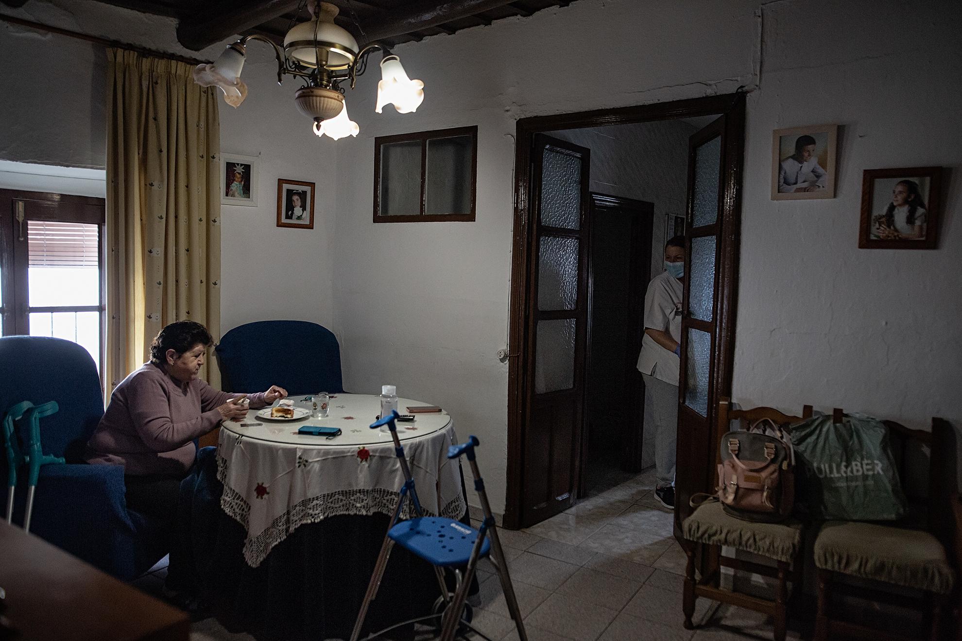 """Puntual a las 9.00 a.m, Mª Carmen del servicio de atención a domicilio del Ayuntamiento de Aracena, acude a su cita con la alegre Luisa de 78 años. Conversan con humor y complicidad mientras Luisa desayuna y Mª Carmen atiende las tareas del hogar. Al final es como una simbiosis en la que las dos tanto se dan como reciben, cada una necesita de la otra en algún sentido. Luisa presume orgullosa de sus 5 nietos y también presume de ser """"una abuela moderna"""". Cada día habla con sus nietos por videollamada, sin ayuda de nadie porque como ella dice: """"Al final es tan fácil como apretar un botón y ya los puedo ver, al menos en la pantalla. Es lo único que llevo mal de salir poco a la calle. No abrazar a mis nietos""""."""
