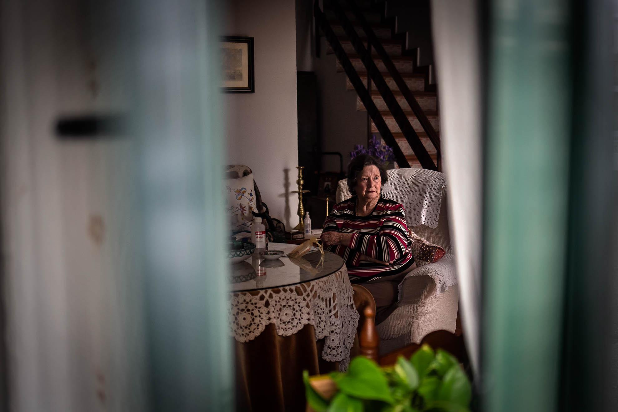 """Botellas de Alcohol sanitario, una mascarilla, el teléfono y los dineros para hacer la compra. Este es el kit de supervivencia al COVID-19 sobre la mesa camilla de Frasca, una encantadora y coqueta mujer de 81 años. Hoy se pintó los labios de rojo porque avisada estaba de que hoy con Rosa vendría una visita. Rosa trabaja en el servicio de ayuda a domicilio del Ayuntamiento de Castillo de las Guardas (Sevilla). Estos días no pueden quedarse tanto con los usuarios, pero aún así le da tiempo a poner la lavadora, hacer la compra, pasar el suelo y arreglar la cocina mientras conversan. """"La gente es muy inconsciente. Yo salgo a dar un paseo por las tardes con mascarilla siempre porque no me fío. Calle arriba, calle abajo y enseguidita pa´ la casa,"""" dice entre preocupada y ofendida con esa gente que no respeta las normas."""