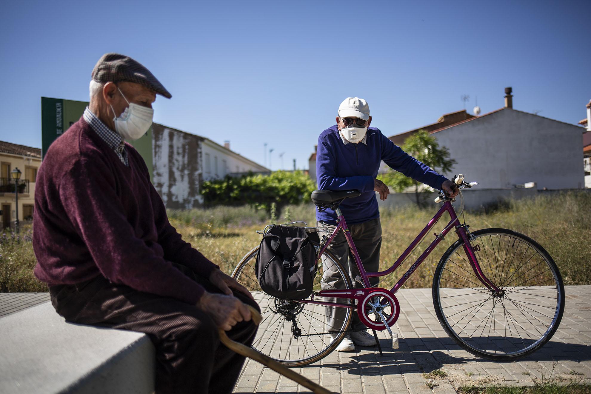 """Son las 11 de la mañana y Andrés, que mañana (por hoy) cumple 90 años, se toma el primer descanso del paseo. Paco, de 92, llega con su bicicleta y se ponen a hablar de los tiempos de entonces, cuando de mocicos en vez de COVID-19 se contagiaban de viruela y sarna. La sarna la curaban con vinagre, azufre y limón, """"porque era lo único que había"""". De la viruela se escapaban por suerte """"porque no había vacuna ni ná"""". Recuerdan aquellos años de hambre y carencias, donde la harina de trigo sabía a arenilla porque algunos vendedores las mezclaban para que pesaran más. Y los días que no había para comer ni aquella harina arenosa, consolaban el dolor de tripa del hambre comiendo algarrobas. Después de tanto pasado este virus no parece ni tan malo. Tocan las campanas de las 12 en la Iglesia de Santa María de Huéscar (Granada). Se acabó el paseo por hoy. Y Andrés se despide de Paco: """"yo estoy bien, pero lo del Paco es que no veas. Míralo, todavía se sube a la bici de correntilla"""". Sin dar tiempo a terminar la frase, Paco ya dobla la esquina como si fuera un chaval."""