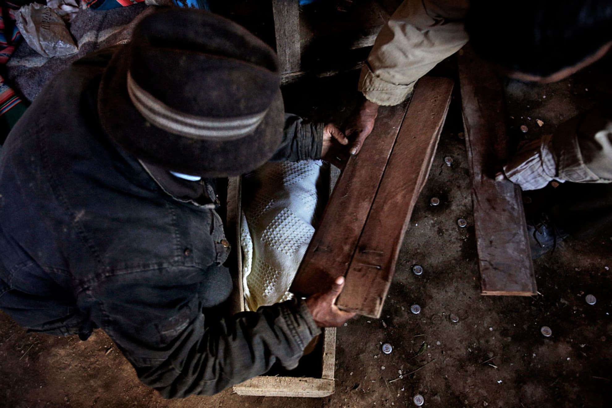 Isidro Guachalla, 60 years old and Antonio Tola Lima, 66 years old, close the coffin of Andrea Paris's baby Mamani, 45 years old, while one of Andrea's daughters, 12 years old, watches them. Isidro and Antonio Tola are neighbors of Andrea's mother in Belén Iquiaca.