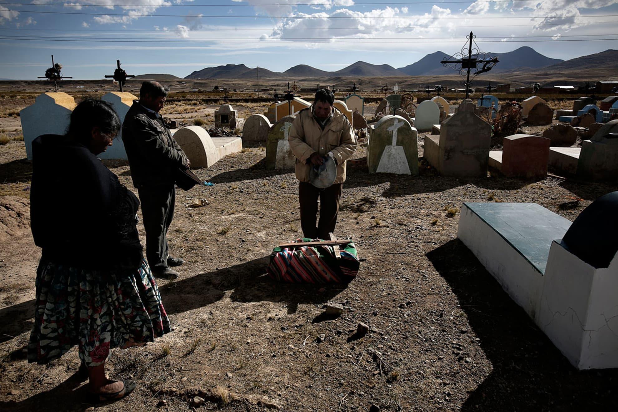 Isidro Guachalla, 60 años, Antonio Tola Lima, 66 años y otra vecina de Belén Iquiaca rezan al rededor del ataúd.