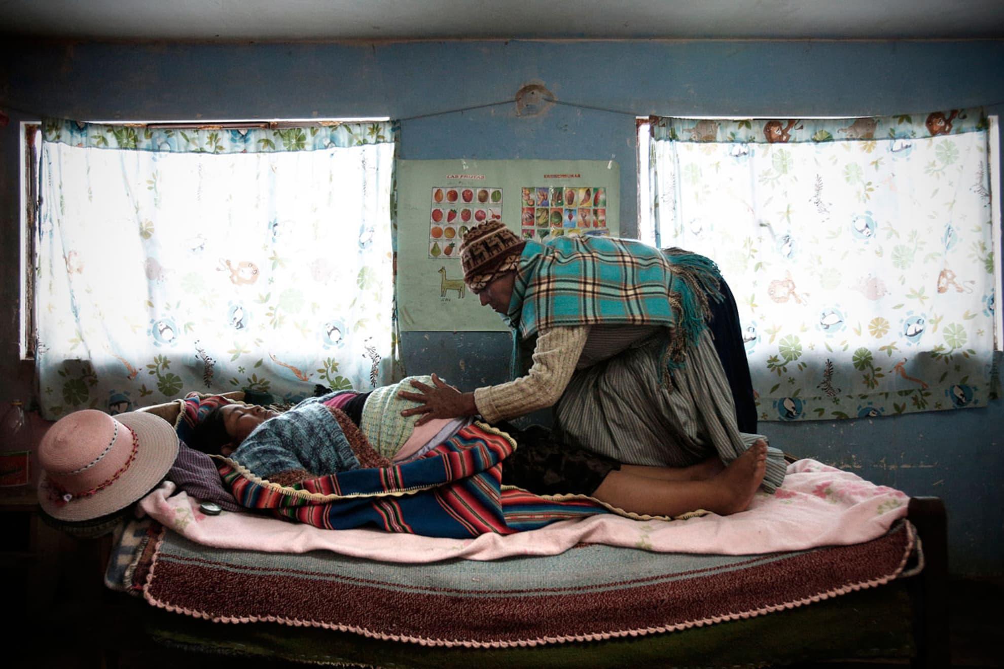 La partera Leonarda Quispe Rojas de 60 años hace masajes a Zenobia Mamani Ramos, 38 años, embaraza de 38 semanas en su casa.