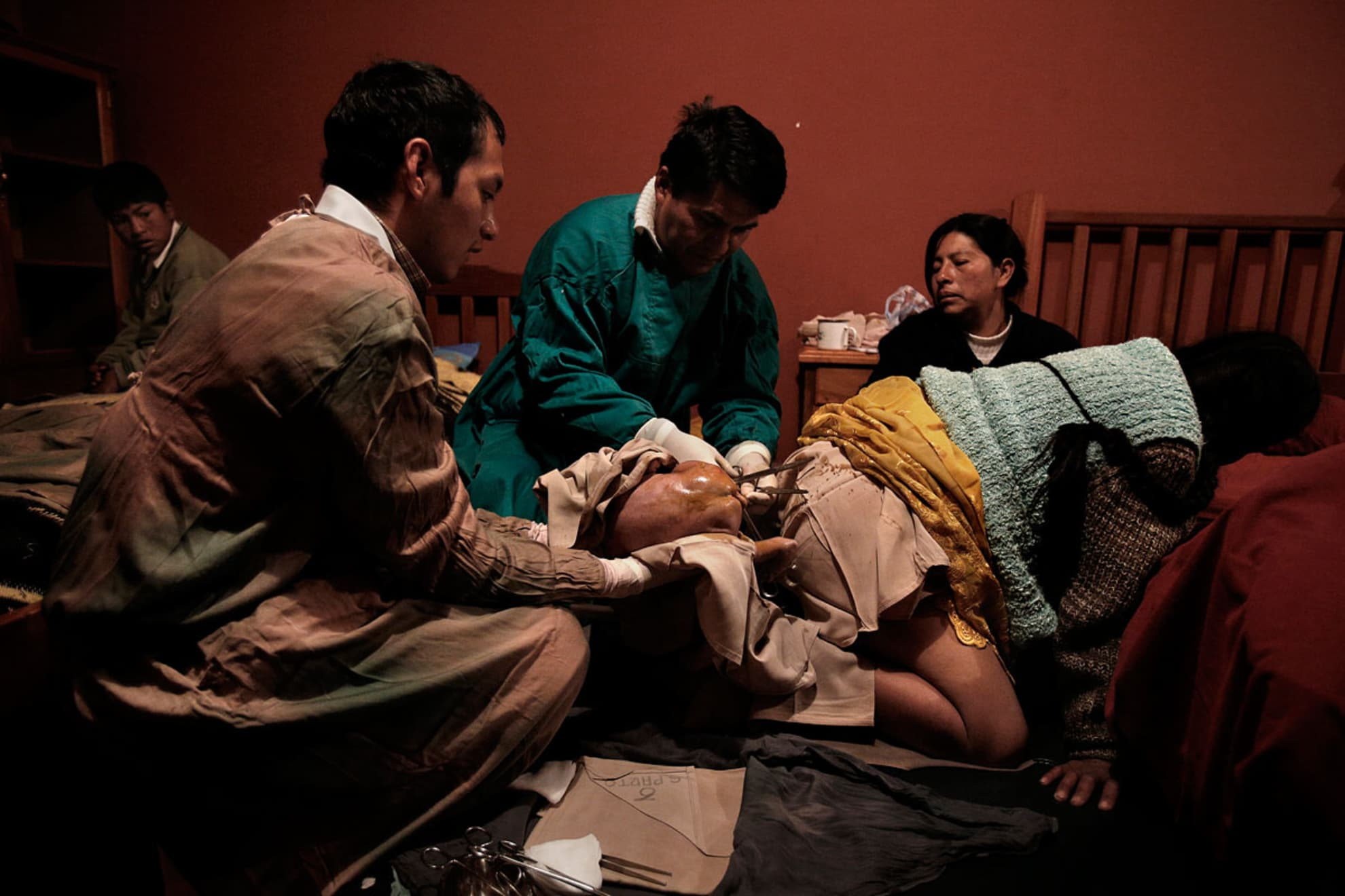 Ceferina Siñani Chiparer, 31 years old, giving birth in the cultural adaptation room of the Patacamaya hospital with the help of medical personnel. Her son Jose Armando, 12 years old, watches.