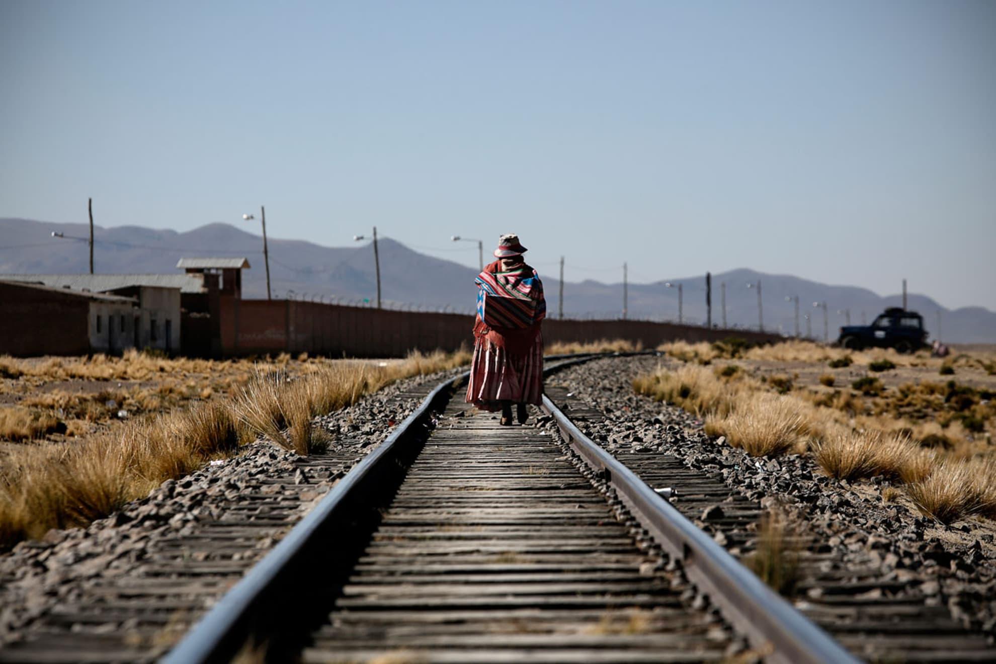 Una mujer camina sobre las vías en Paracamaya.