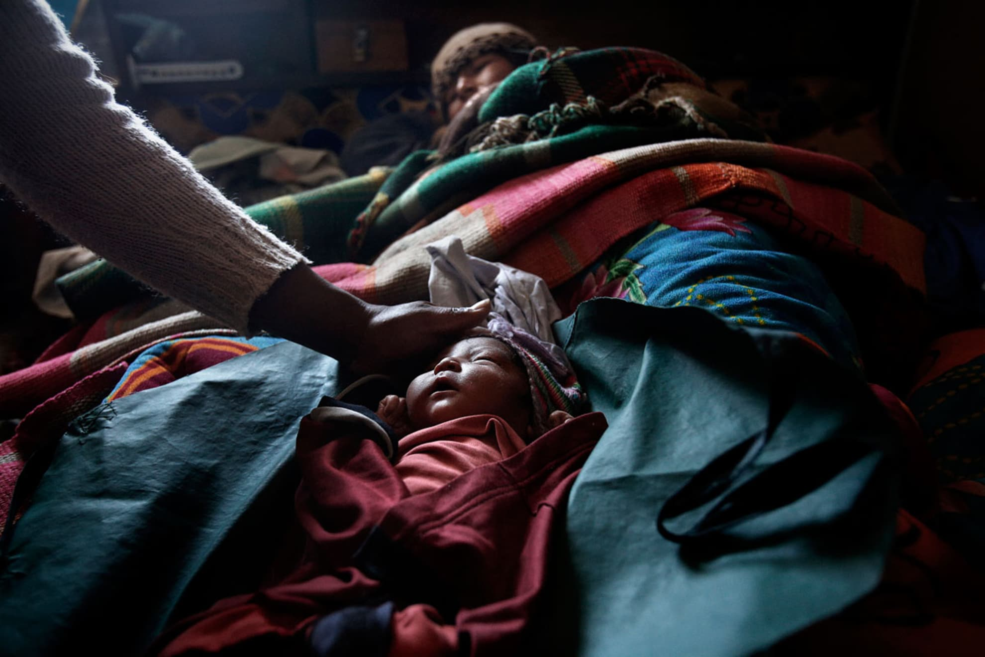 Elsa Quispe Matías de Fila a lado de su bebe un día después del parto. Elsa tuvo el bebe en su casa con la ayuda de su marido Eduardo Fila Apaza porque no confiaba en el medicina del hospital. Tiene otros cinco hijos, todos nacidos en su casa.