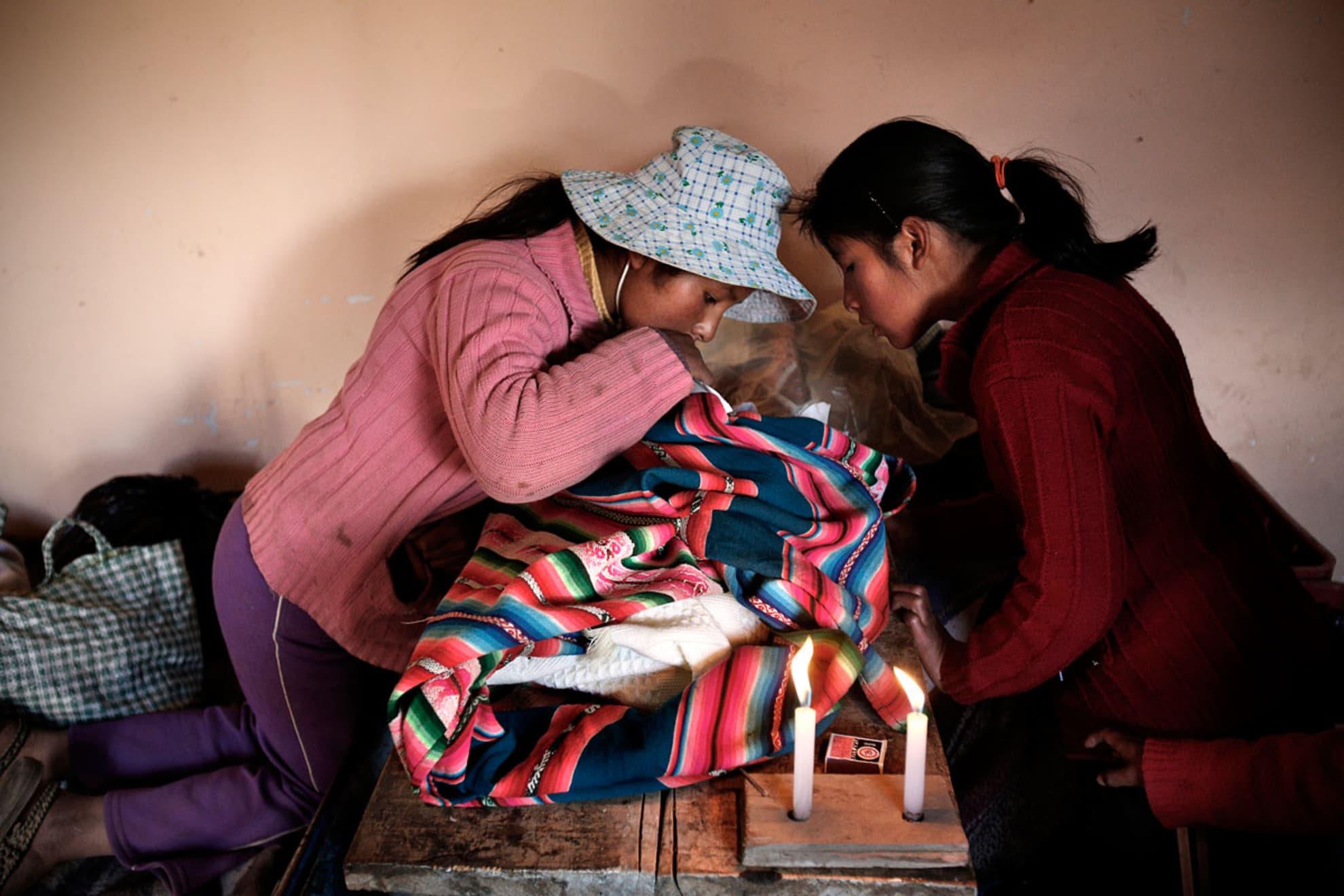 Las hijas de Andrea Paris Mamani observan el cuerpo del bebe que acaba de dar a luz su madre. El bebe nació muerto.