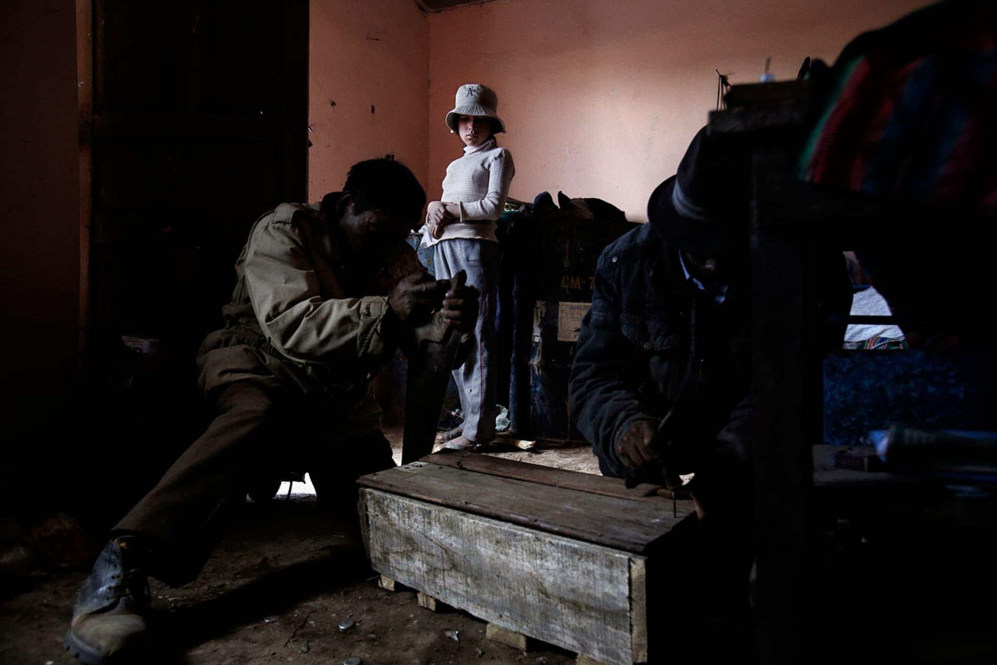 Isidro Guachalla, 60 años y Antonio Tola Lima, 66 años cierran el ataúd del bebe de Andrea Paris Mamani, 45 ans, mientras una de las hijas de Andrea, 12 años, los observa. Isidro y Antonio Tola son vecinos de la madre de Andrea en Belén Iquiaca.