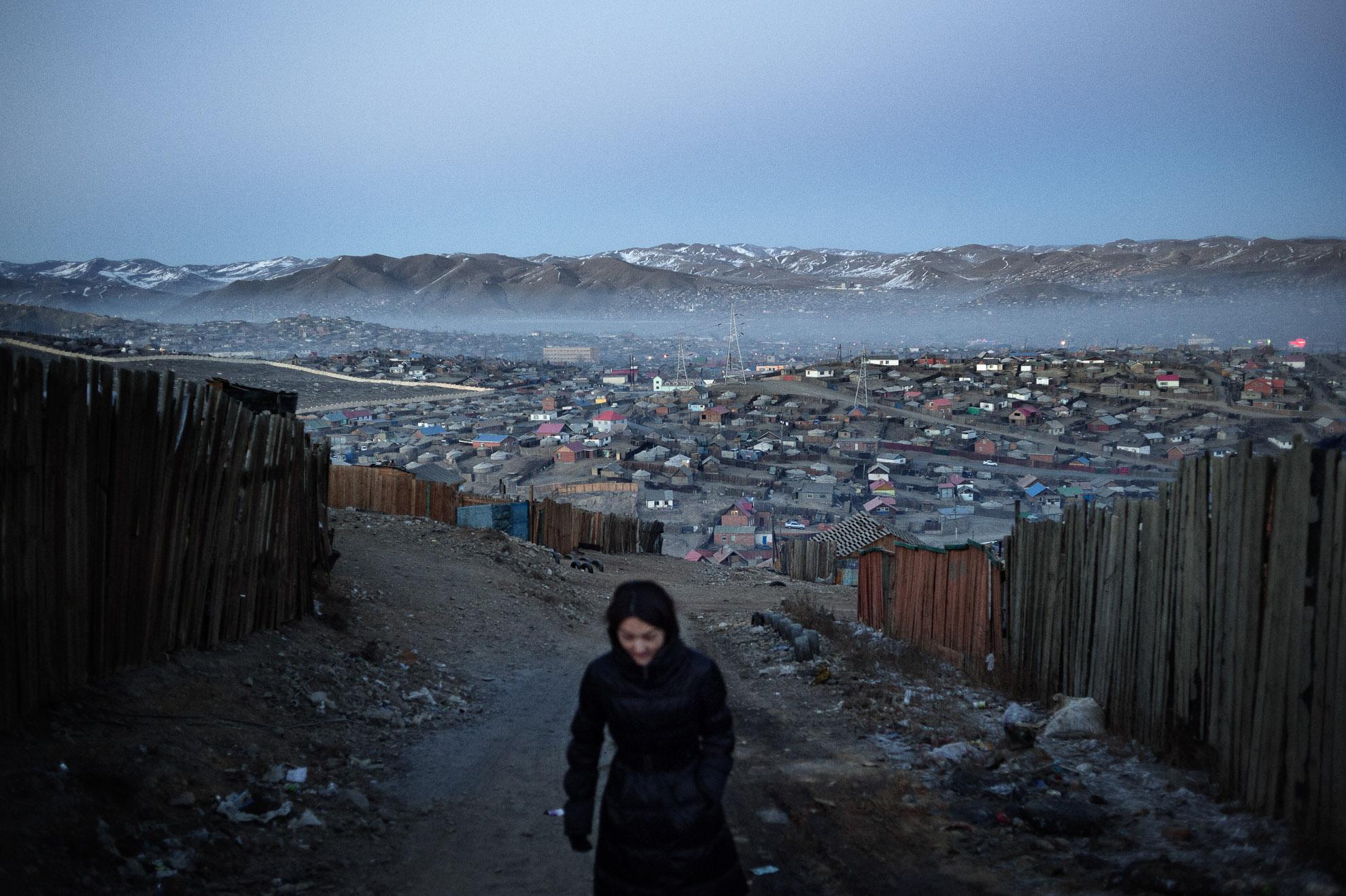 """Mongolia. Ulán Bator, vista del distrito ger. En Mongolia la mitad de la población vive hacinada en la capital, que cuenta con más de un millón doscientos mil ciudadanos. La mitad de ellos vive en el barrio marginal desarrollado alrededor de la ciudad, conocido como """"distrito ger"""", que toma su nombre de la tienda tradicional mongola llamada ger y que se extiende por toda la ciudad. En los últimos 20 años, la población de la capital se ha duplicado: esta reciente migración ambiental ha traído consigo un alto nivel de desempleo y pobreza. De hecho, el barrio de los ger se ha desarrollado sin ningún tipo de planificación urbana, agua corriente o electricidad; así, los pastores, obligados a abandonar las zonas rurales, llegan a la ciudad tras toda una vida en los pastos, no están capacitados para asumir ningún tipo de trabajo y acaban viviendo una vida de penurias."""