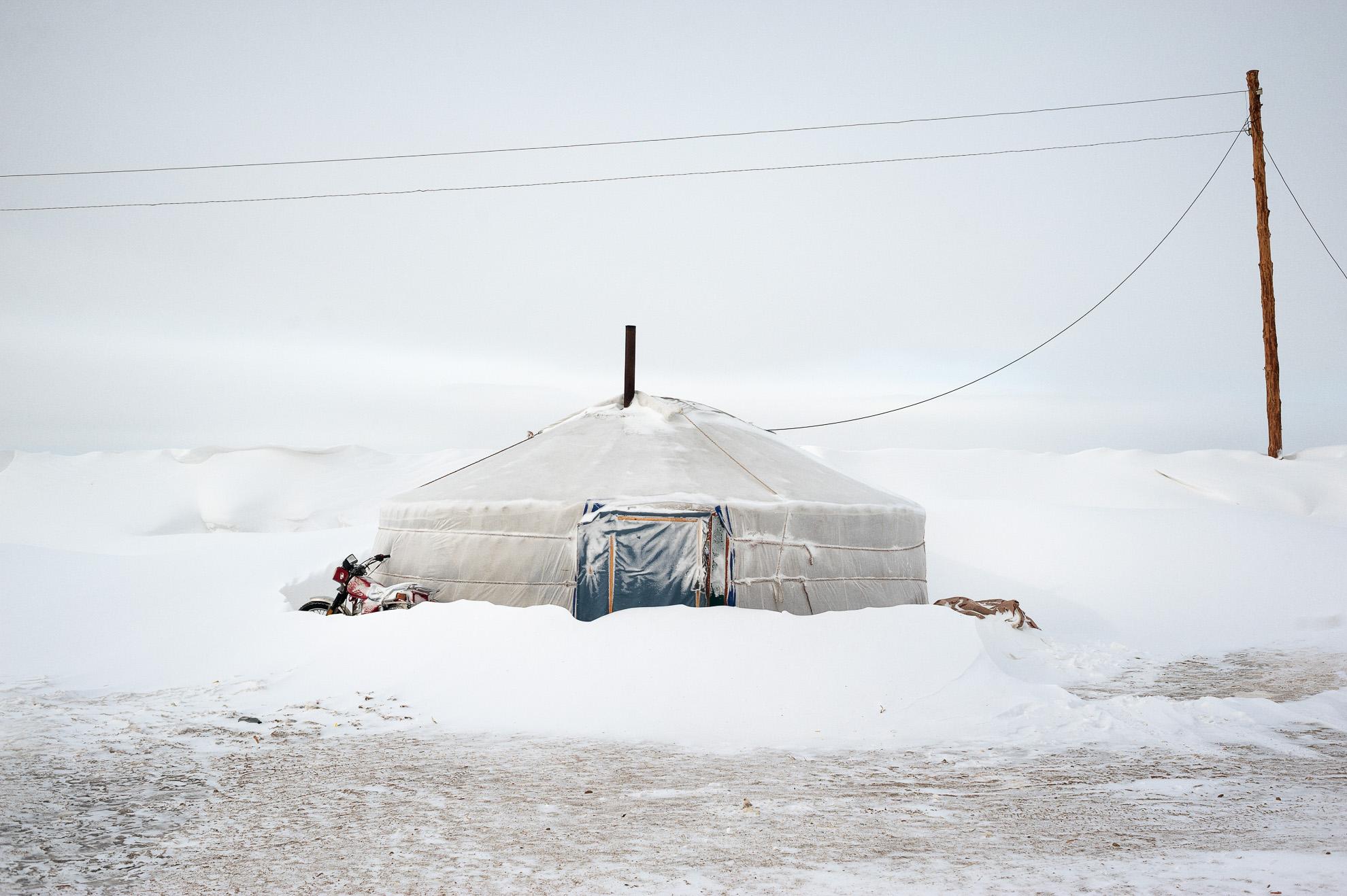 Mongolia, provincia de Arkhangay. Un gher abandonado y sumergido por la nieve. Este gher se levanta cerca del de la familia Tsamba y ha sido abandonado por una familia de pastores. A pesar de los duros inviernos en la provincia mongola de Arkhangai, la familia Tsamba sigue viviendo allí, luchando junto a su rebaño de ovejas. Las severas condiciones invernales, conocidas como dzud, han sido las responsables de la muerte de la mitad del rebaño de la familia, que llegó a tener 2.000 ovejas, en los últimos tres inviernos. Recientemente, en busca de pastos más cálidos, los Tsambas se trasladaron desde la provincia de Bulgan, en el norte, a esta región cercana a un pueblo del centro de Mongolia llamado Ulziit.