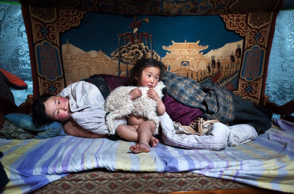 Mongolia, provincia de Arkhangay. Erdene Tuya, de 29 años, con su hijo de 3 años llamado Tuvchinj (abraza a un corderito que duerme con ellos). Acaban de despertarse mientras su marido Batgargal salió a echar un vistazo al rebaño con el otro hijo llamado Azjargal, de 6 años. En la provincia mongola de Arkhangai, la familia Tsamba vive al límite, luchando contra los duros inviernos junto a su rebaño de ovejas. Las severas condiciones invernales, conocidas como dzud, han sido las responsables de la muerte de la mitad del rebaño de la familia, que llegó a tener 2.000 ovejas, en los últimos tres inviernos. Recientemente, en busca de pastos más cálidos, los Tsambas se trasladaron desde la provincia de Bulgan, en el norte, a esta región cercana a un pueblo del centro de Mongolia llamado Ulziit.