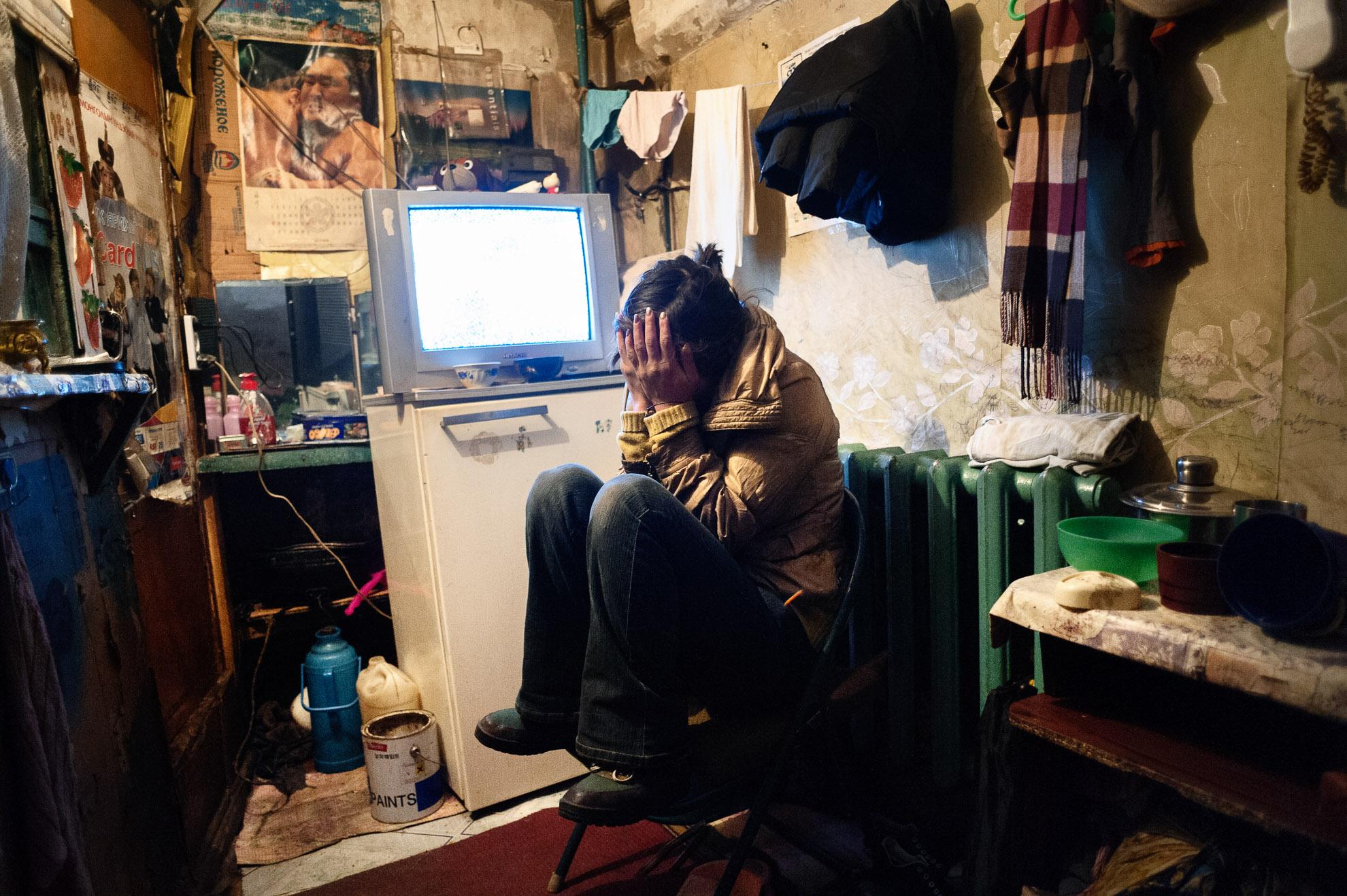 Mongolia, Ulán Bator. Dyun Erdene, ex pastora de 26 años, está sentada en el reducido espacio que comparte con su familia -su padre de 55 años, antiguo pastor, su madre, una hermana y su sobrino de 4 años- en Ulán Bator. Solía vivir con su familia en Gobi-Ugtaal, en la provincia de Dunggobi, pero durante el dzud perdieron sus 150 animales y, por tanto, decidieron trasladarse a la ciudad. Está embarazada, pero su novio la dejó y ahora está sola. Su madre es guardiana de un apartamento y están viviendo en una habitación superpoblada bajo la escalera del mismo edificio donde trabaja su madre. Consiguieron este espacio gracias al trabajo de su madre (la única que trabaja en la familia). Pagan un pequeño alquiler, pero solo pueden ahorrar un poco de dinero para su alimentación básica diaria. Su padre ha sido pastor durante toda su vida y no puede hacer ni encontrar ningún otro trabajo.