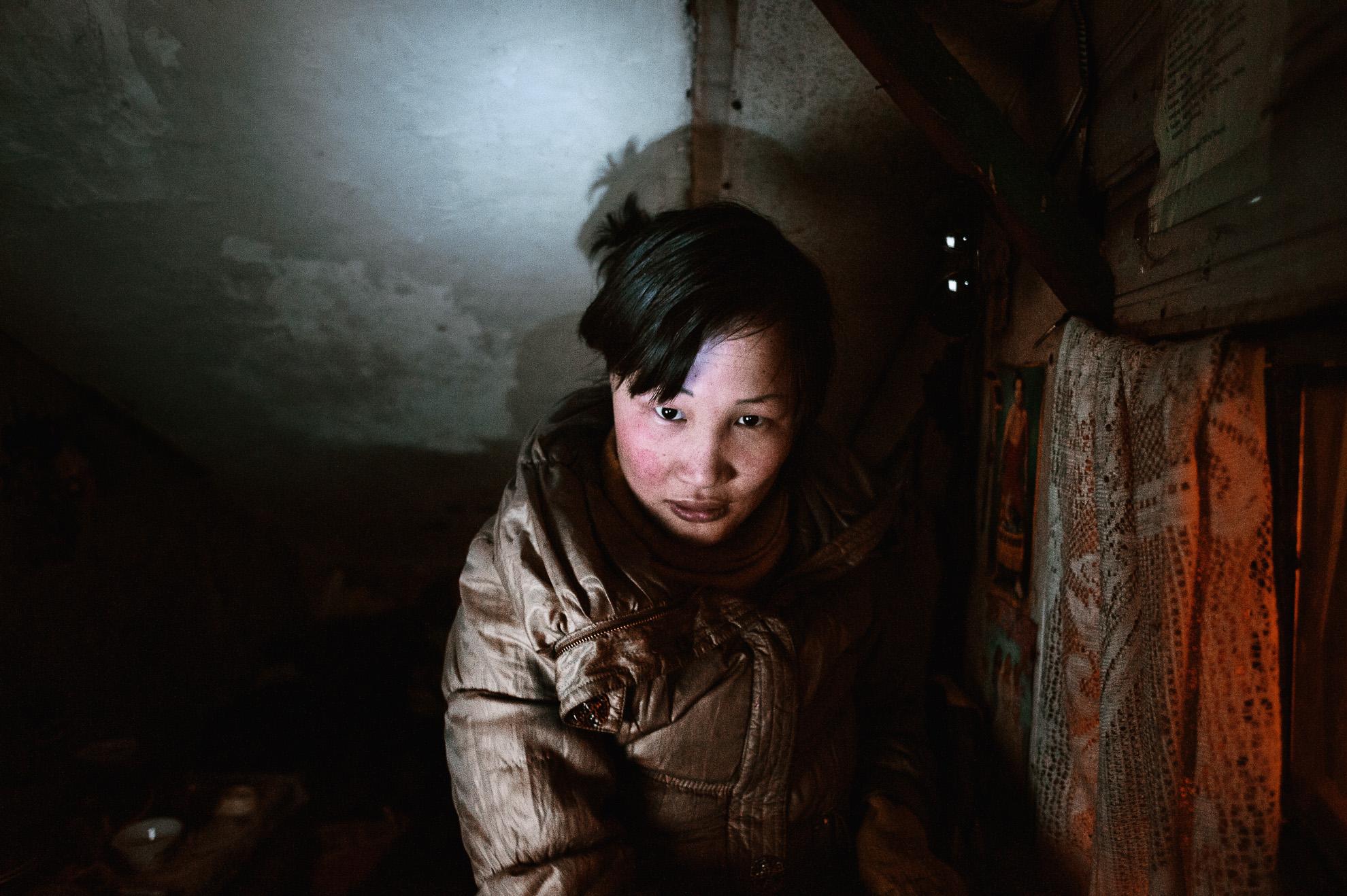 Mongolia, Ulán Bator. Dyun Erdene, de 26 años, antigua pastora, en el reducido espacio que comparte con su familia -su padre, de 55 años y antiguo pastor, su madre, una hermana y su sobrino de 4 años- en Ulán Bator. Antes vivía con su familia en Gobi-Ugtaal, en la provincia de Dunggobi, pero durante el dzud perdieron sus 150 animales y, por tanto, decidieron trasladarse a la ciudad. Está embarazada, pero su novio la dejó y ahora está sola. Su madre es guardiana de un apartamento y están viviendo en una habitación superpoblada bajo la escalera del mismo edificio donde trabaja su madre. Consiguieron este espacio gracias al trabajo de su madre (la única que trabaja en la familia). Pagan un pequeño alquiler, pero solo pueden ahorrar un poco de dinero para su alimentación básica diaria. Su padre ha sido pastor durante toda su vida y no puede hacer ni encontrar ningún otro trabajo.