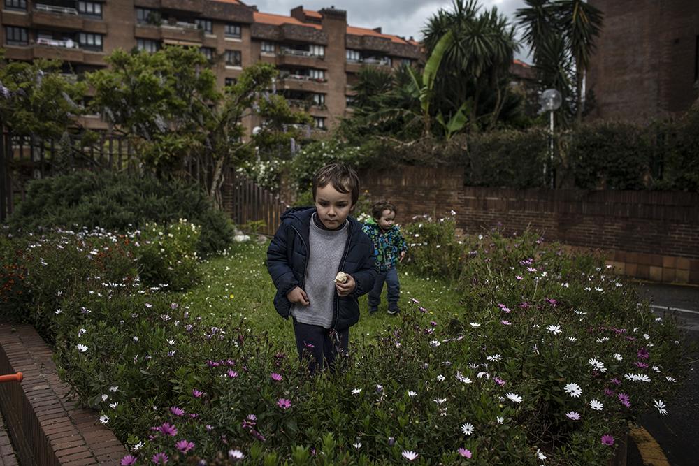 Teo, 5, y Simón, 2, juegan sobre una jardinera frente a la urbanización donde residen tras pasear con su padre durante la hora que permite la norma vigente en España desde ayer día 26 de Abril. Gijón, Asturias, España.