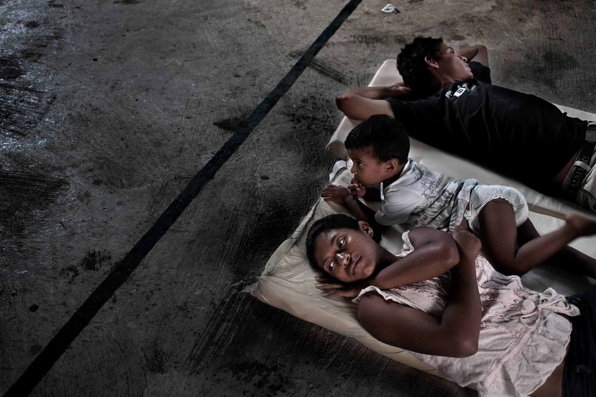 Coatzacoalcos, Veracruz, México, 2011. Esta localidad es un importante nudo ferroviario. Una familia de Honduras descansa en una iglesia a las afueras de la ciudad de Coatzacoalcos. Están esperando al próximo tren.