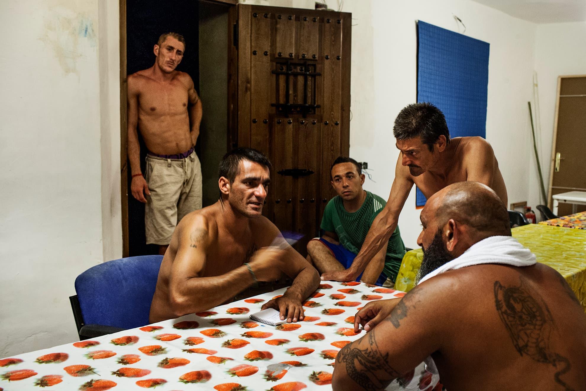 Chule y Fernando hablan de los planes de ampliar y construir mas habitaciones en La Casa de la Buena Vida. Mascota mira desde el umbral y David escucha y observa los planos.