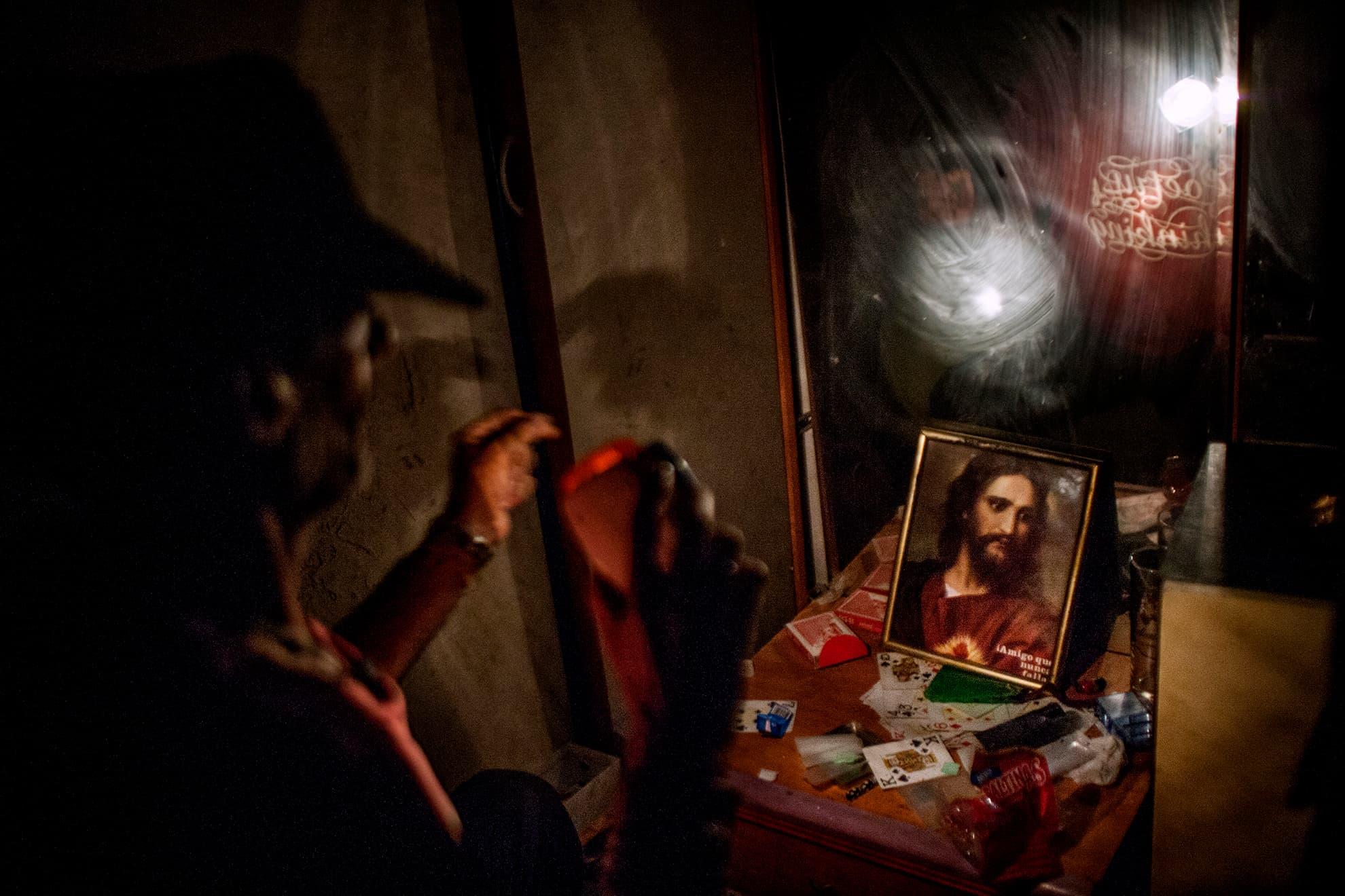 Jerónimo, que fue profesor, habla con una foto de Jesús y enciende una luz ante el espejo. Está aquí por problemas de drogas y de salud mental. La religión es un tema importante en La Casa porque muchos residentes dependen de la ayuda de su fe y su creencia en Dios para rehacer sus vidas.