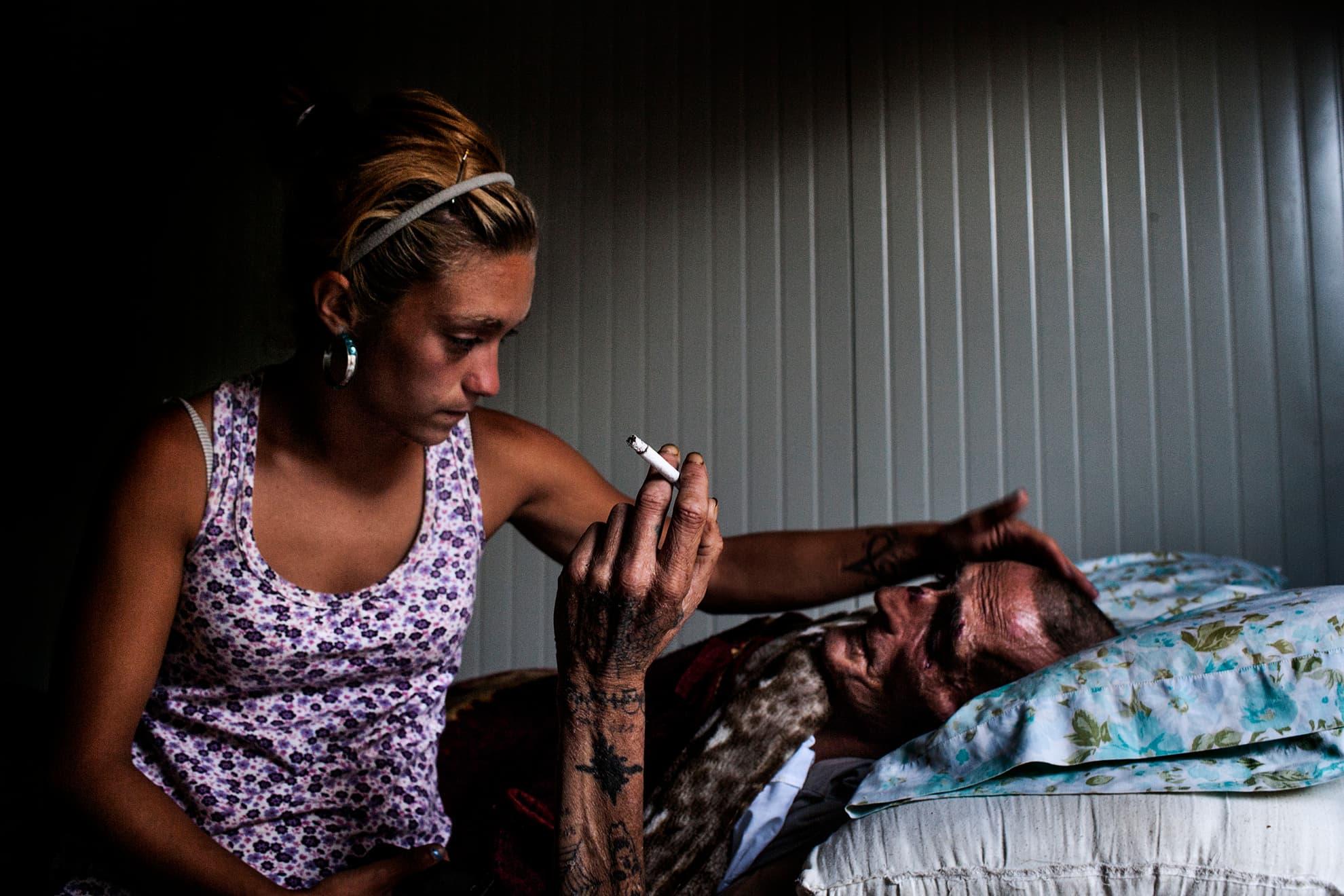 """Ana, una de las residentes más jóvenes de La Casa de la Buena Vida, cuidando de Juan. Juan tiene 49 años, tiene SIDA y hace poco recibió el alta hospitalaria porque los médicos consideran que ya no pueden hacer nada más por él. No tiene familia, aparte de la """"familia"""" y el apoyo que le proporciona La Casa."""