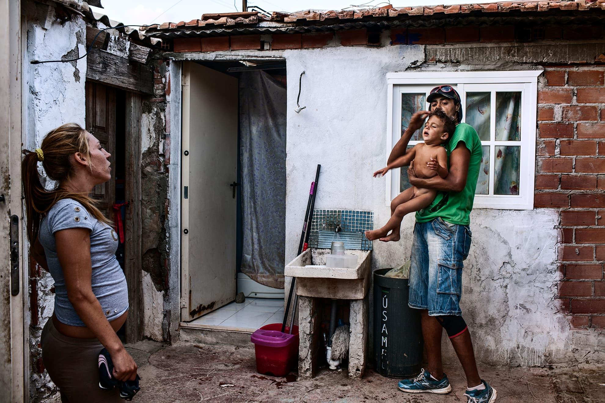 María observa mientras uno de los residentes de La Casa de la Buena Vida asea a Luis para salir a dar una vuelta a la Feria de Málaga. Luis, de 3 años, María y Mascota viven en una habitación pequeña de La Casa de la Buena Vida.