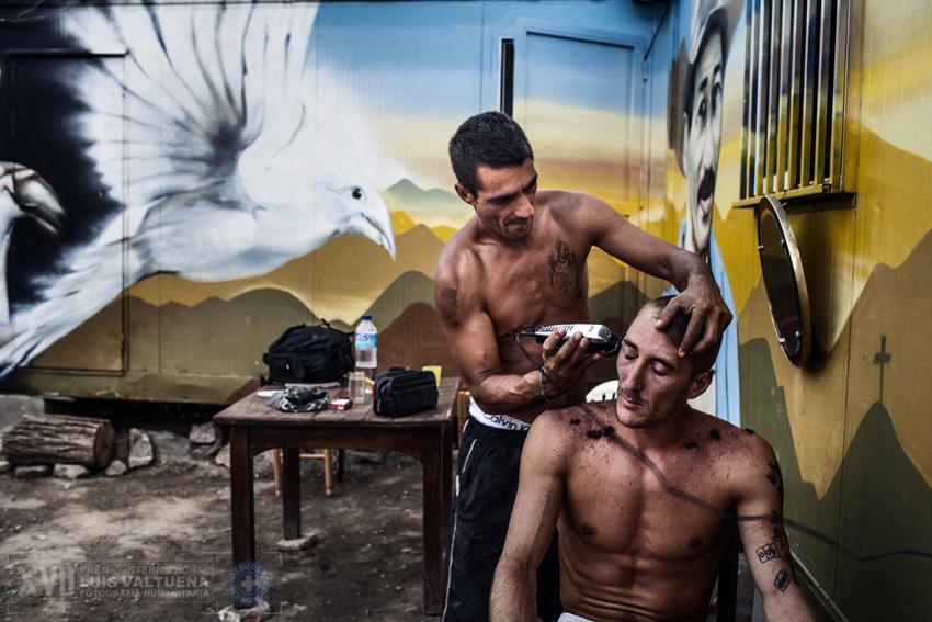 Fernando corta el pelo a Mascota delante de uno de los nuevos contenedores de La Casa de la Buena Vida. Las paredes están decoradas por grafiteros locales. Los contenedores son una donación privada y permiten alojar a seis personas más.
