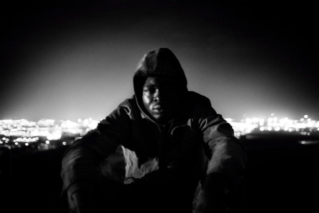 Narcisse, de Camerún, momentos antes de intentar saltar la valla. Detrás, las luces de la ciudad de Melilla. Narcisse consiguió esa noche cruzar a Melilla.