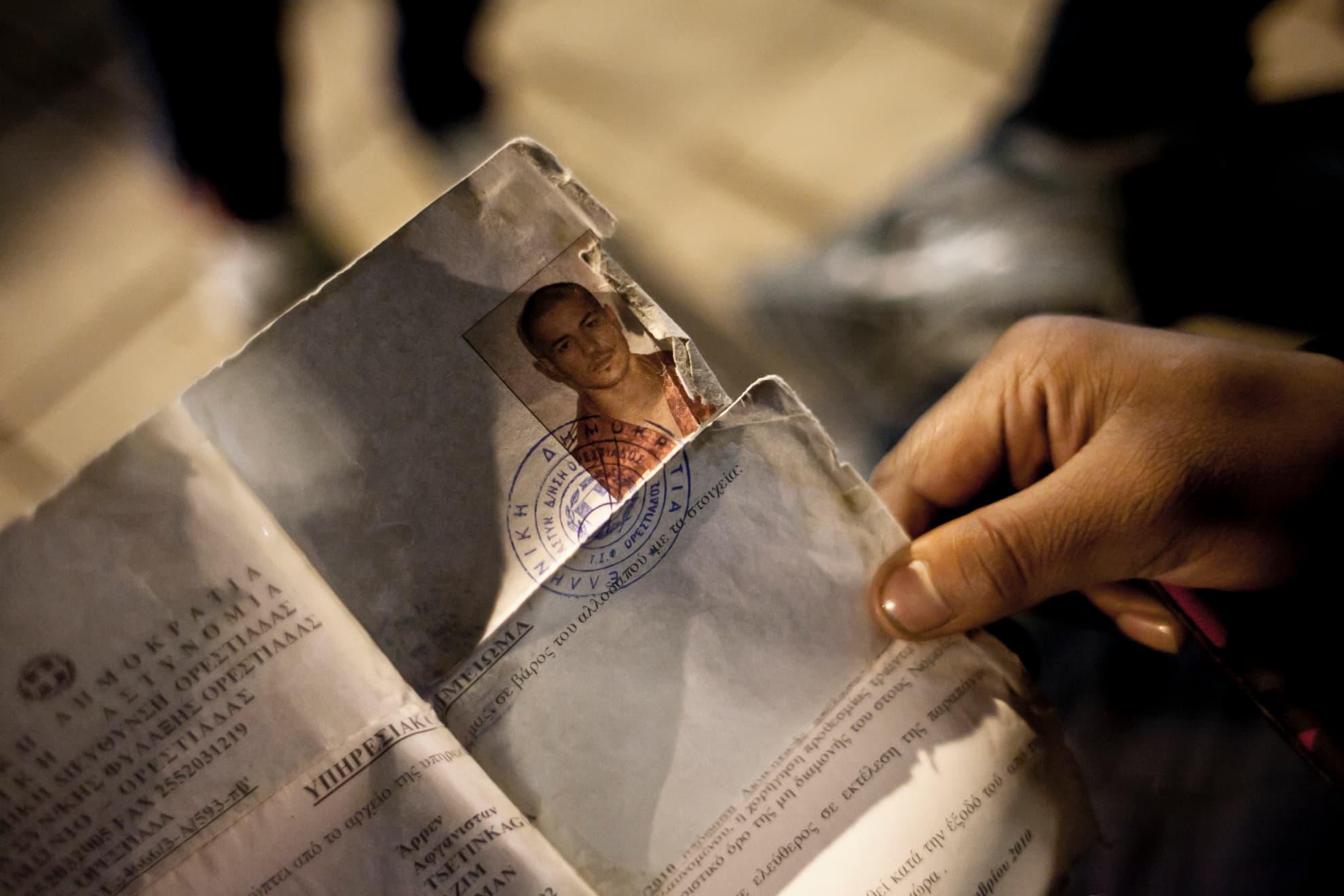 """Un joven observa su """"tarjeta blanca"""". Muchas personas migrantes son arrestadas por su situación irregular y permanecen detenidas hasta su expulsión. Cuando son devueltas a la calle, les entregan este documento con la orden de abandonar el país por sus propios medios en el plazo de un mes."""