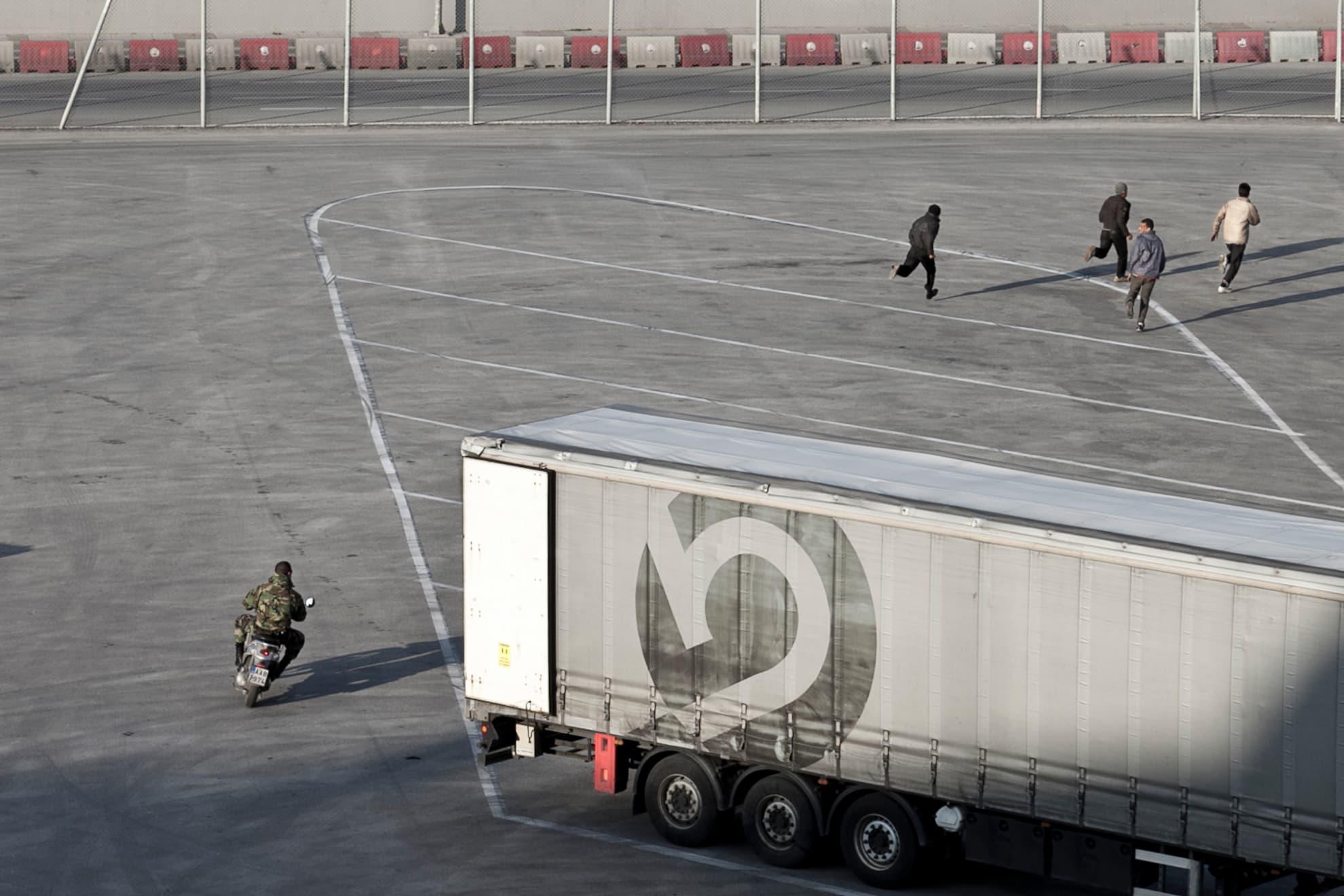 Un agente de la Guardia Costera persigue a un grupo de migrantes que intentaba esconderse en un camión de mercancías con destino a Italia. En los puertos griegos, la vigilancia por parte de unidades especiales se incrementa durante el embarque de vehículos en los ferris.