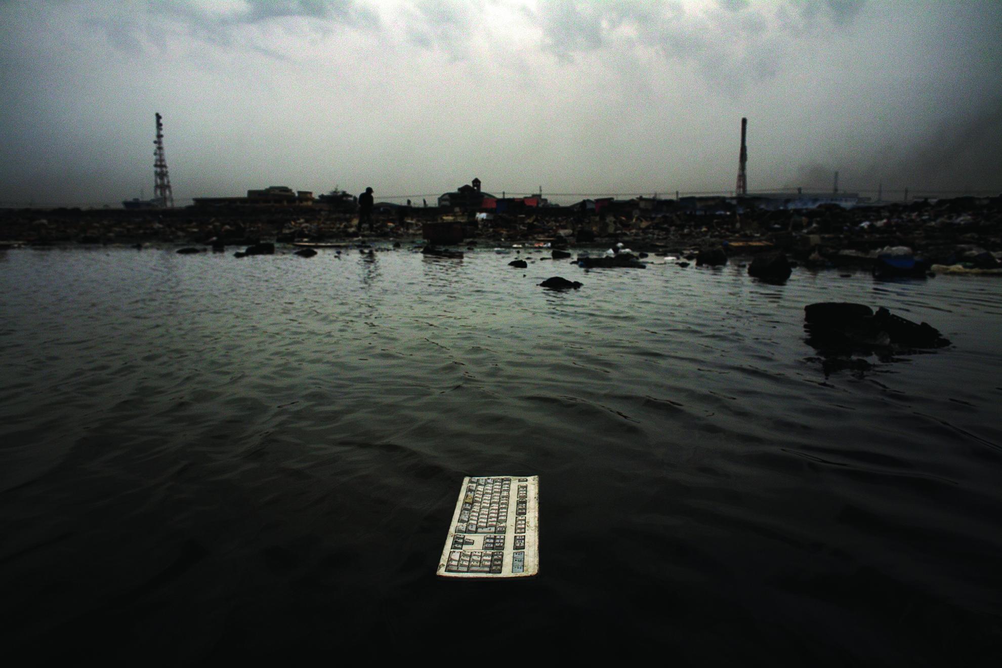 Un teclado yace en una laguna contaminada en el vertedero de Agbogbloshie en Accra, Ghana. Residuos electrónicos desechados en África Occidental por los Estados Unidos y Europa; muchos de los elementos tóxicos contenidos en estos residuos suponen una amenaza para la vida humana, las reservas de agua y el medio ambiente.