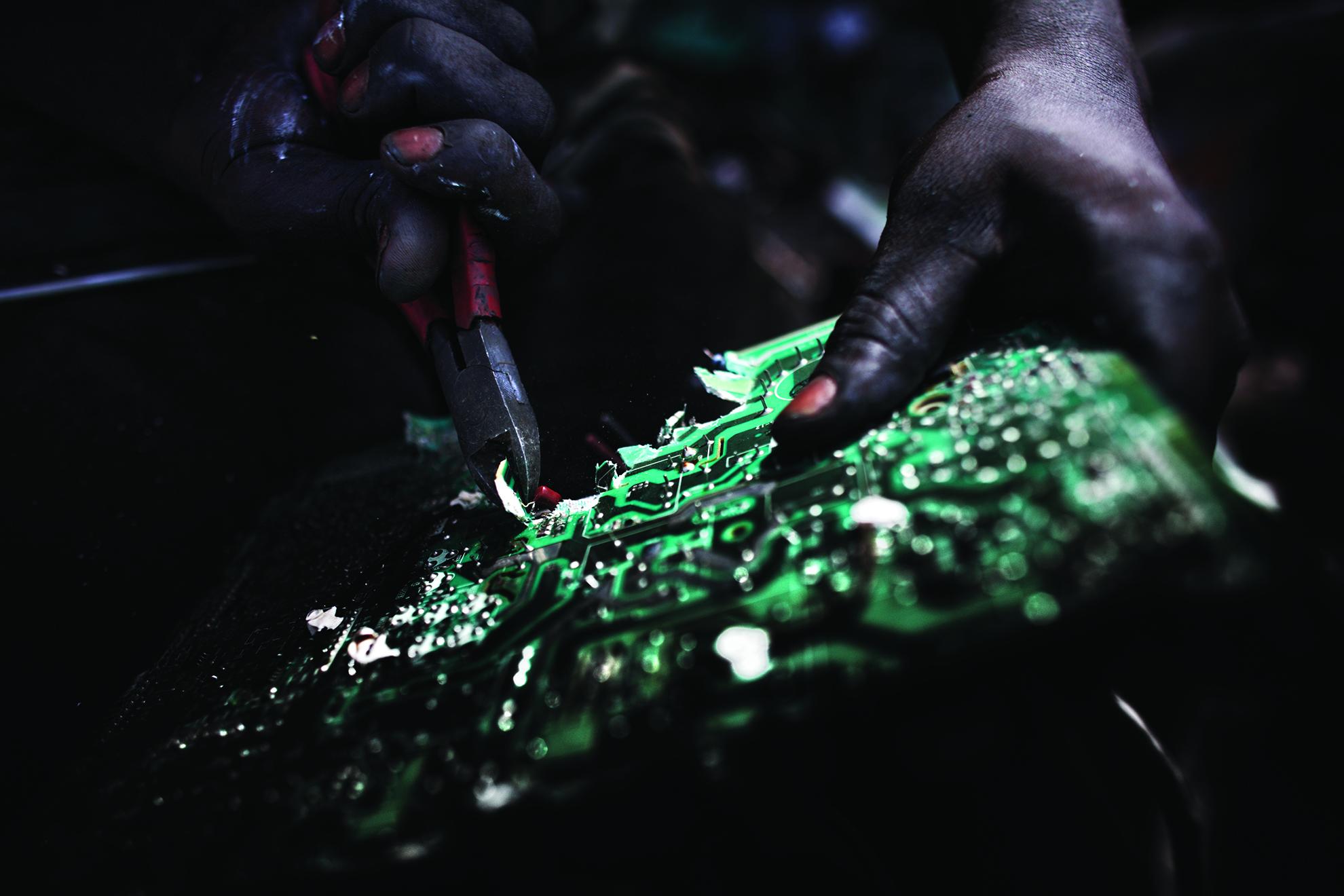 Un hombre rompe una tarjeta de circuitos para recuperar sus componentes en el vertedero de Agbogbloshie.