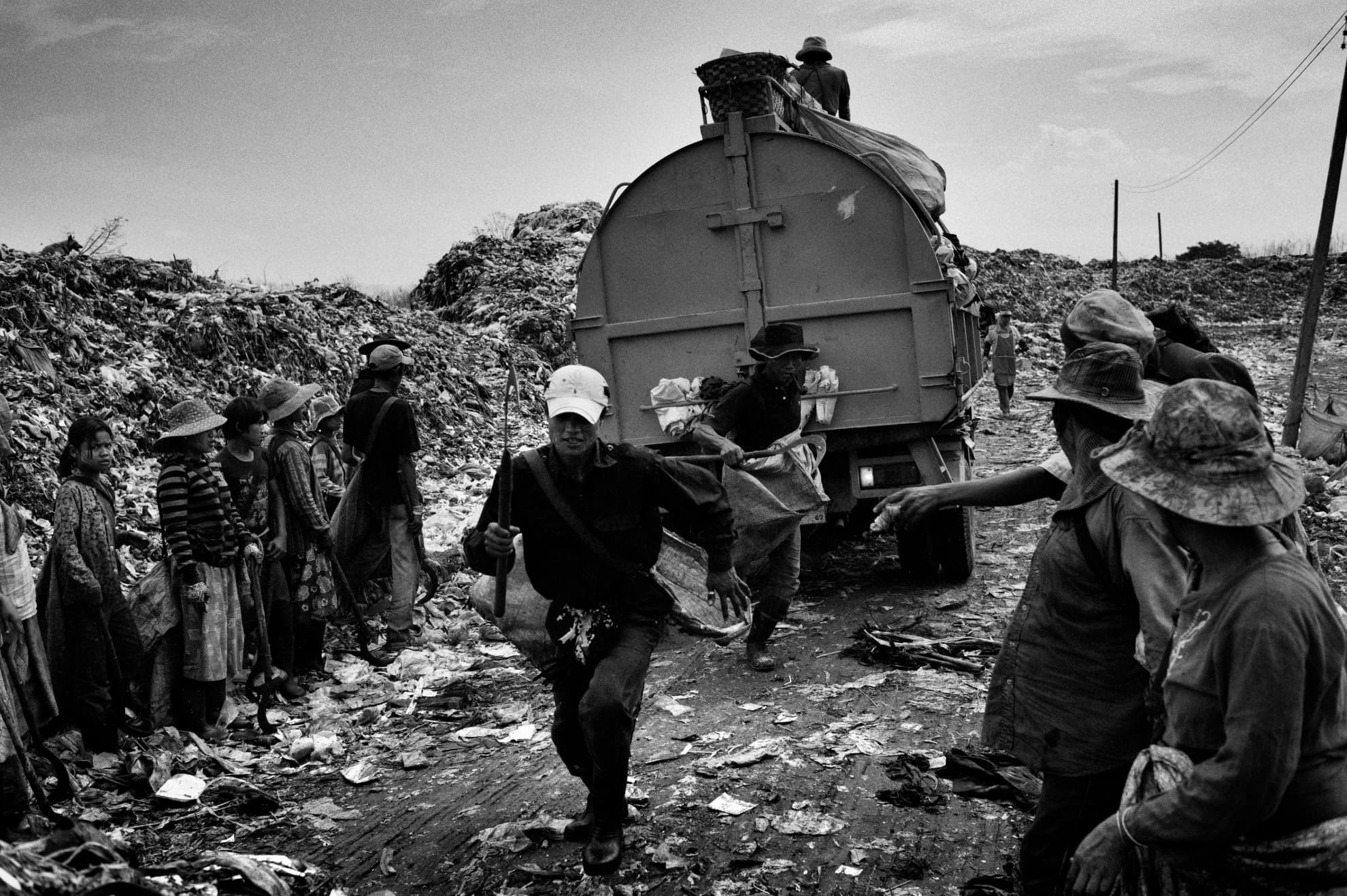 A rubbish lorry full of refuse that has not been previously sorted in the local recycling plant arrives at the dump. As it promises a more profitable harvest of recyclable material, people rush to be the first to sort through it.