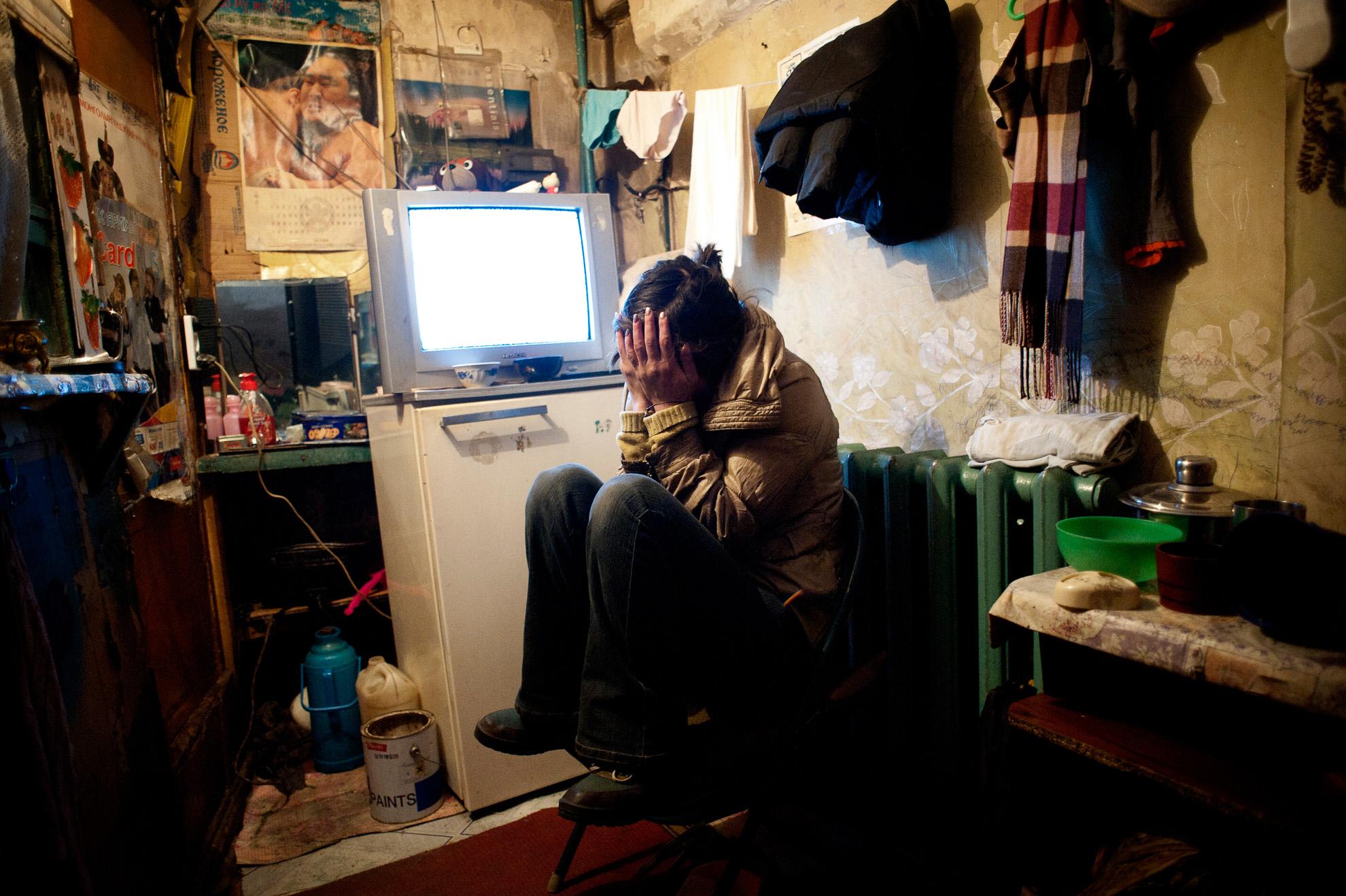 Dyun Erdene, 26 años, antigua pastora, sentada en el estrecho espacio que comparte con su familia: su padre, de 55 años, antiguo pastor; su madre, una hermana y su sobrino de 4 años, en Ulan Bator. Solía vivir con su familia en Gobi-Ugtaal en la provincia de Dunggobi, pero durante el dzud de 2010 perdieron sus 150 animales, por lo que decidieron trasladarse a la ciudad. Está embarazada, pero su novio la dejó y ahora está sola. Su madre es portera de un edificio de apartamentos. La familia vive apretada en un cuarto bajo las escaleras en el mismo edificio.