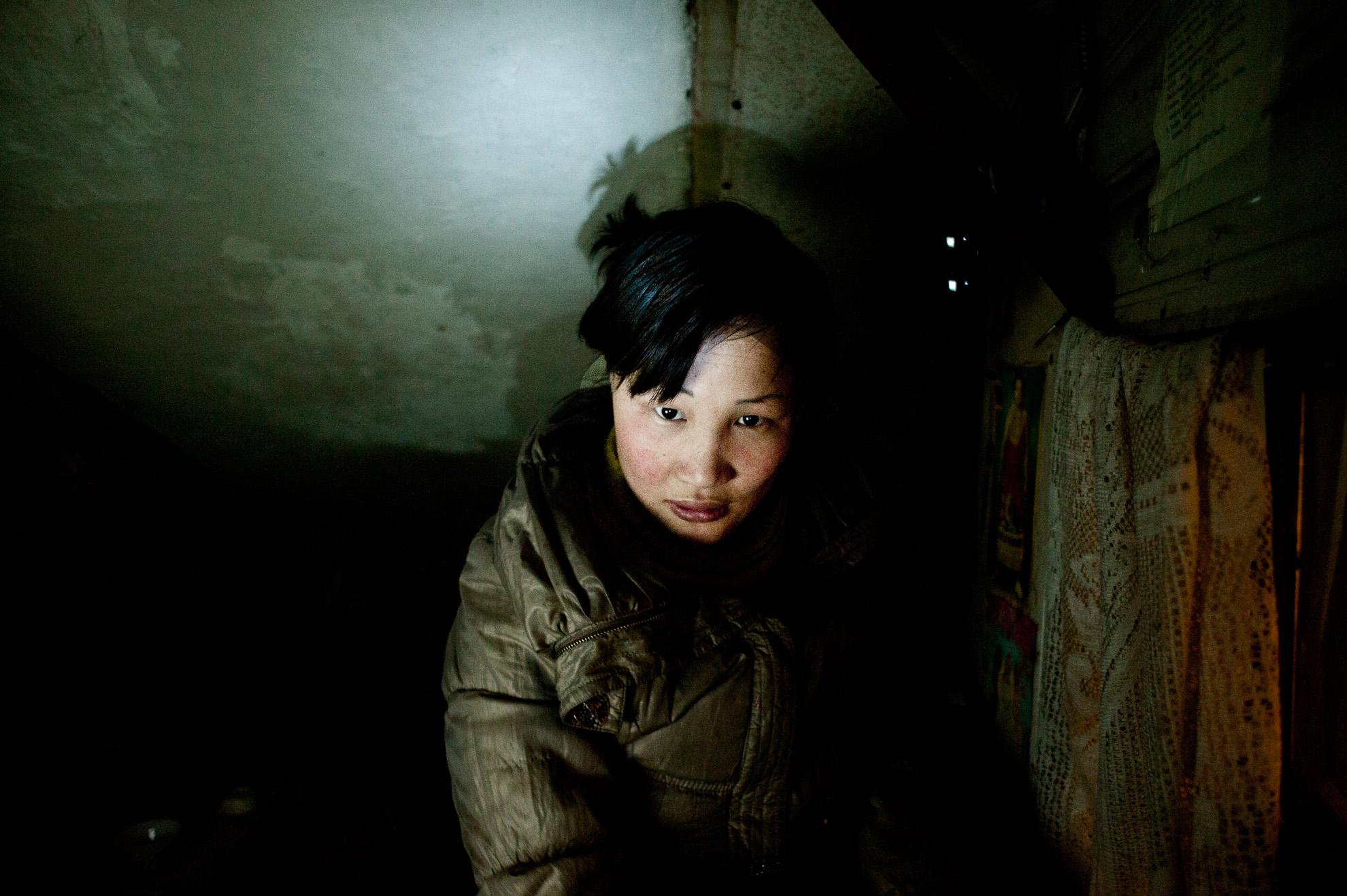 Dyun Erdene, 26 años, antigua pastora, sentada en el espacio que comparte con su familia. Consiguieron este espacio gracias al trabajo de la madre (la única que trabaja en la familia). Deben pagar solo un modesto alquiler, y así pueden ahorrar algo de dinero para los alimentos básicos. Su padre ha sido pastor toda su vida: es analfabeto y carece de conocimientos para desarrollar otro tipo de trabajo.