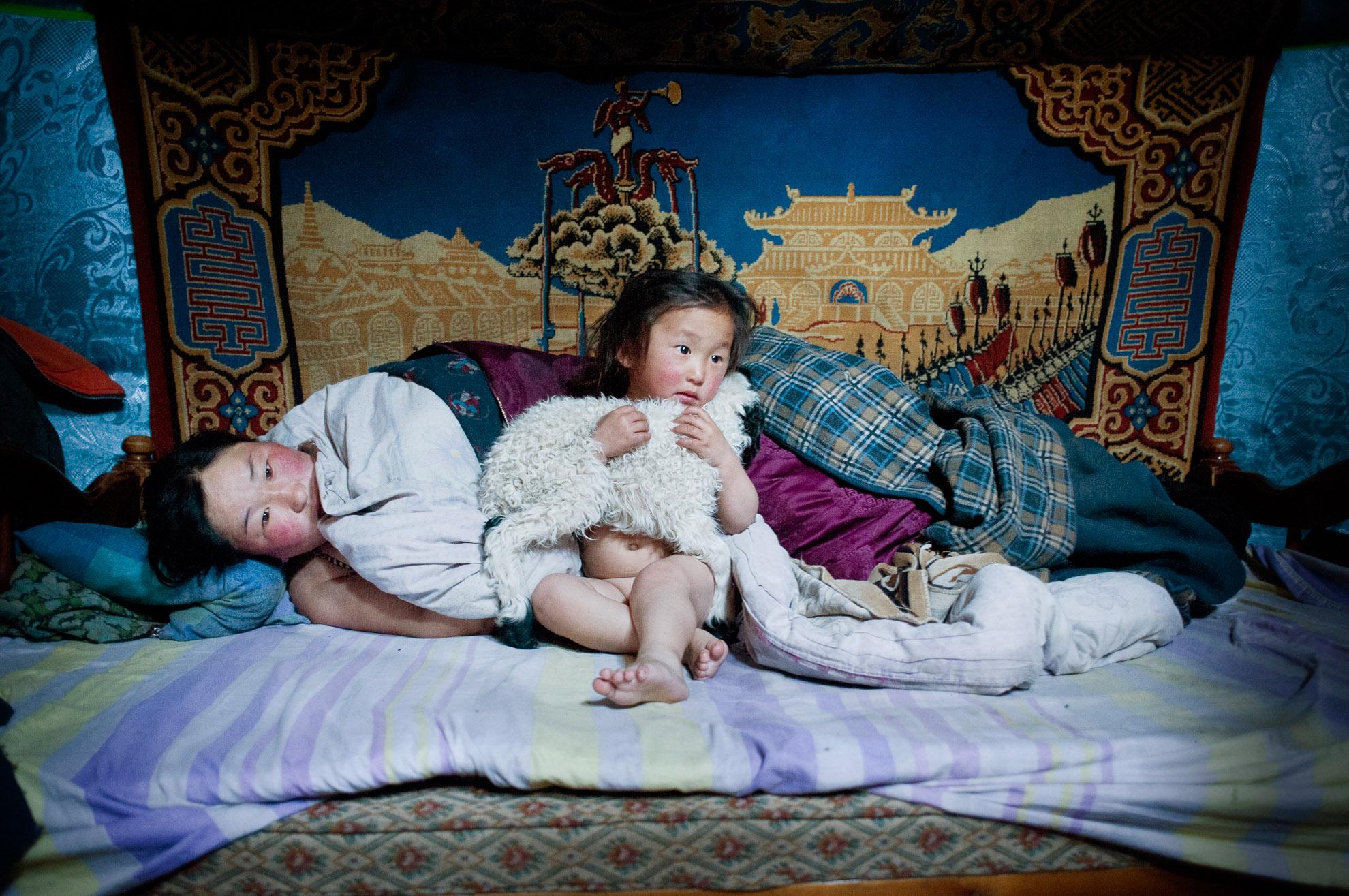 Erdene Tuya, junto a su hijo de 3 años llamado Tuvchinj (que abraza a un borreguito que duerme con ellos) acaba de despertarse, mientras su marido Batgargal ha salido a echarle un vistazo al rebaño con su otro hijo, Azjargal, de 6 años.