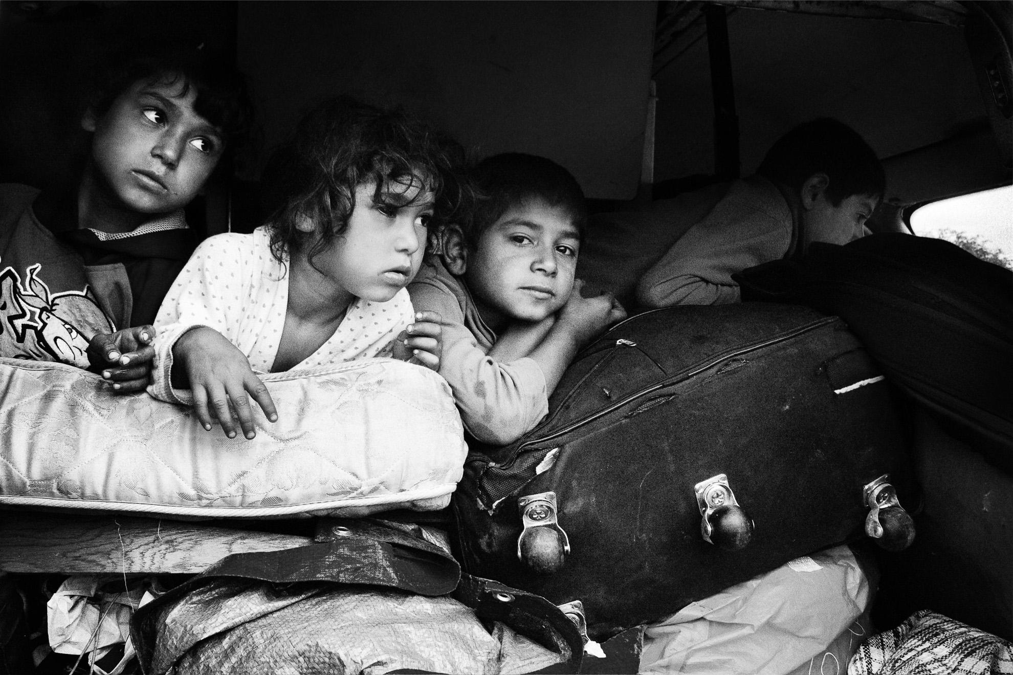 Ante la inminente llegada de la policía para desalojar el campamento, unas familias romaníes deciden marcharse voluntariamente. En la furgoneta viajarán durante dos días a Rumania, 4 adultos y 7 niños. A falta de espacio los niños viajarán encima de las maletas.