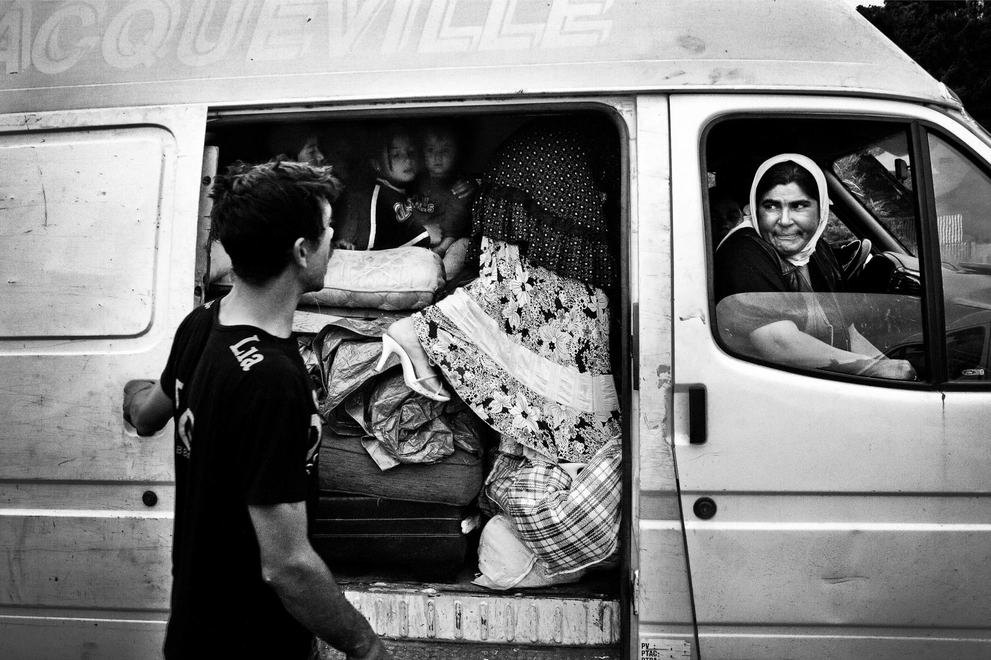 Dos familias romanís abandonan su campamento para regresar a Rumanía antes de que la policía los expulse. Horas antes, los interceptó la policía en la calle y les preguntaron dónde estaban residiendo. Tienen miedo de que les fichen y ya no puedan regresar a Francia. En la furgoneta viajan 11 personas, 4 adultos y 7 niños. En la foto un hombre despide a su familia. Él se queda para acabar de vender la chatarra que queda en el campamento.