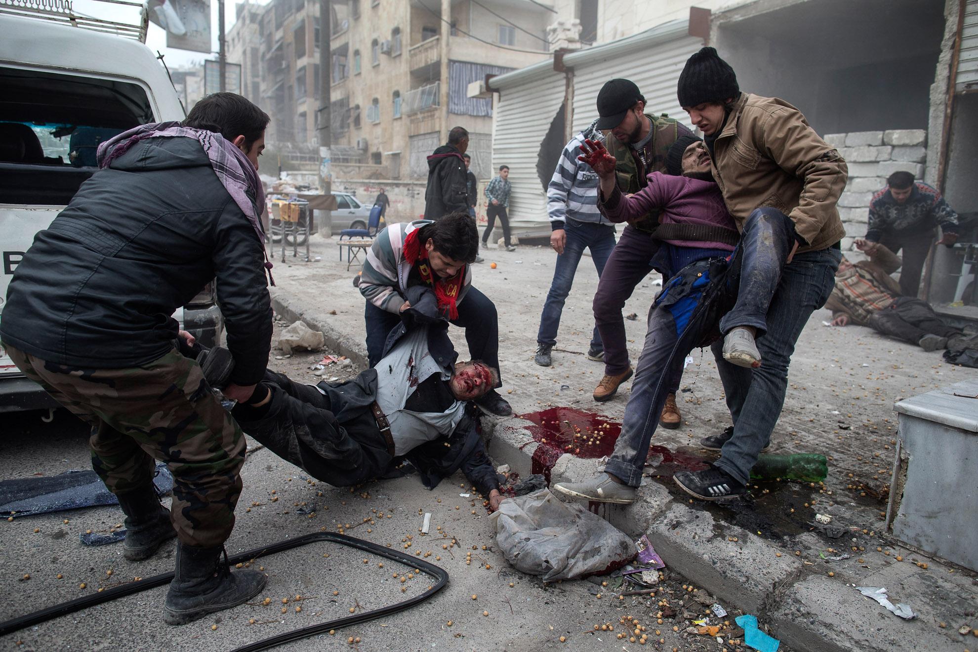 Alepo, Siria. 13-01-2013. Un hombre ayuda a transportar el cadáver de un civil muerto tras un ataque con morteros en el barrio de Saif al-Dawlah de Alepo. Seis personas murieron y dieciséis resultaron heridas.