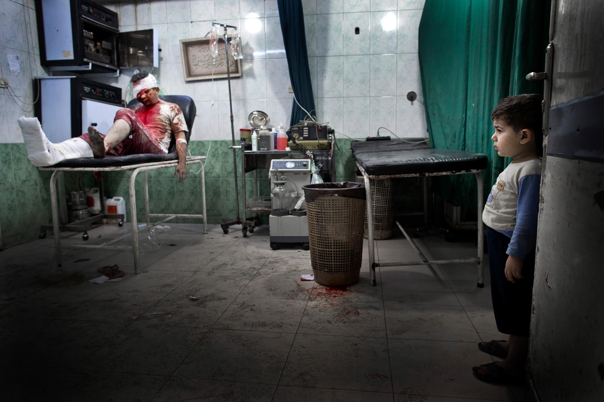 Alepo, Siria. 15-10-2012. Un niño en el hospital de Dar al-Shifa mira a los pacientes heridos. El hombre herido fue trasladado al hospital junto a su esposa embarazada. Ambos están en estado crítico.