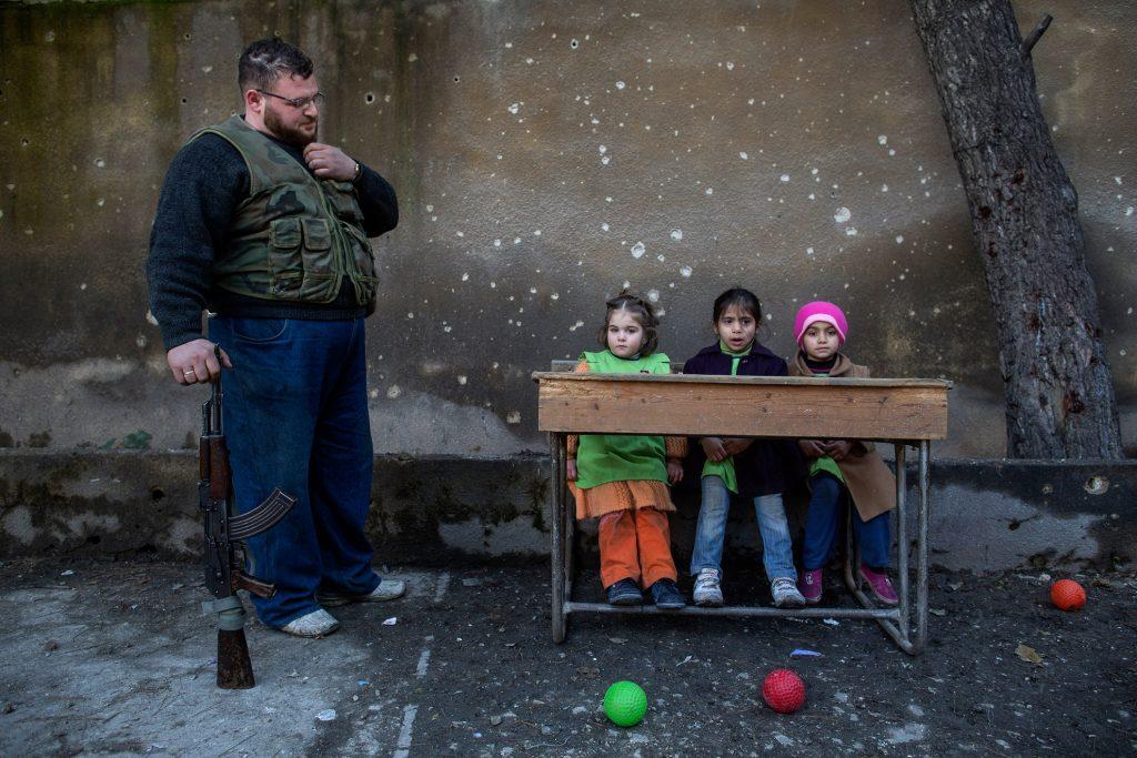 Alepo, Siria. 13-01-2013. Niños sentados en los pupitres de la escuela Al-Tawheed de Alepo. La mayoría de las escuelas de Alepo están cerradas. Debido a la falta de calefacción y electricidad algunas clases se trasladan afuera.