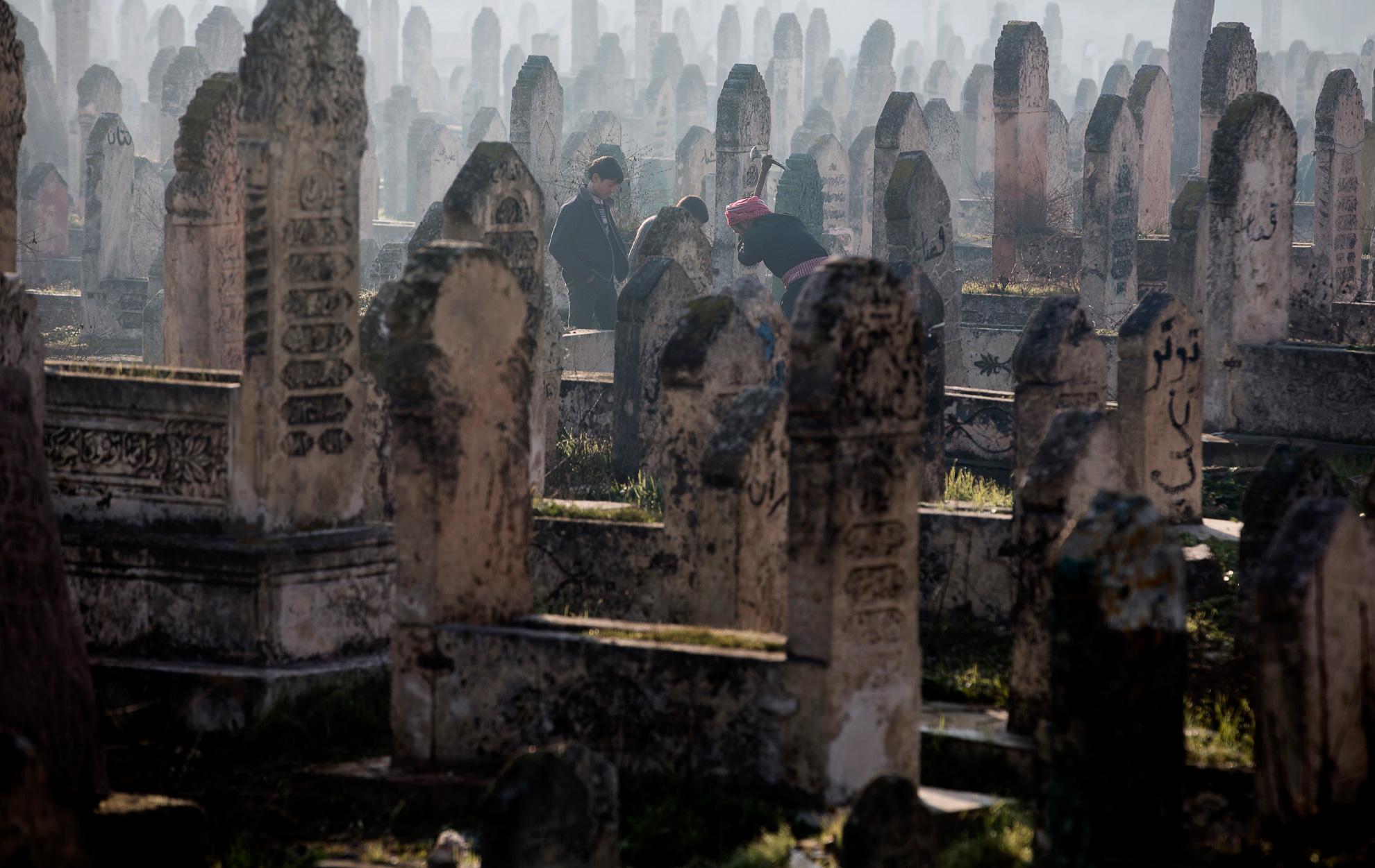 Alepo, Siria. 15-01-2013. Un hombre cava una tumba en un cementerio de Alepo ante la mirada de sus hijos.