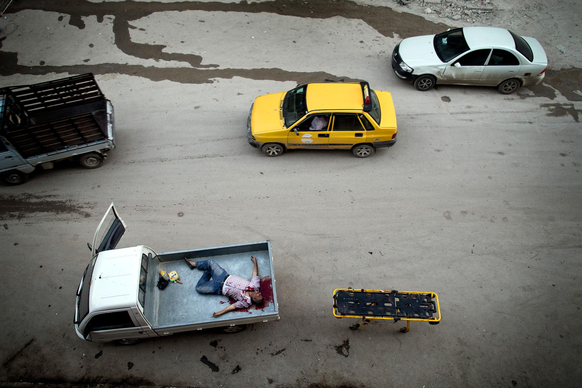 Alepo, Siria. 15-10-2012. Un civil muerto fuera del hospital de Dar al-Shifa en Alepo es depositado en una camioneta para llevarlo con su familia. Fue alcanzado por un francotirador.