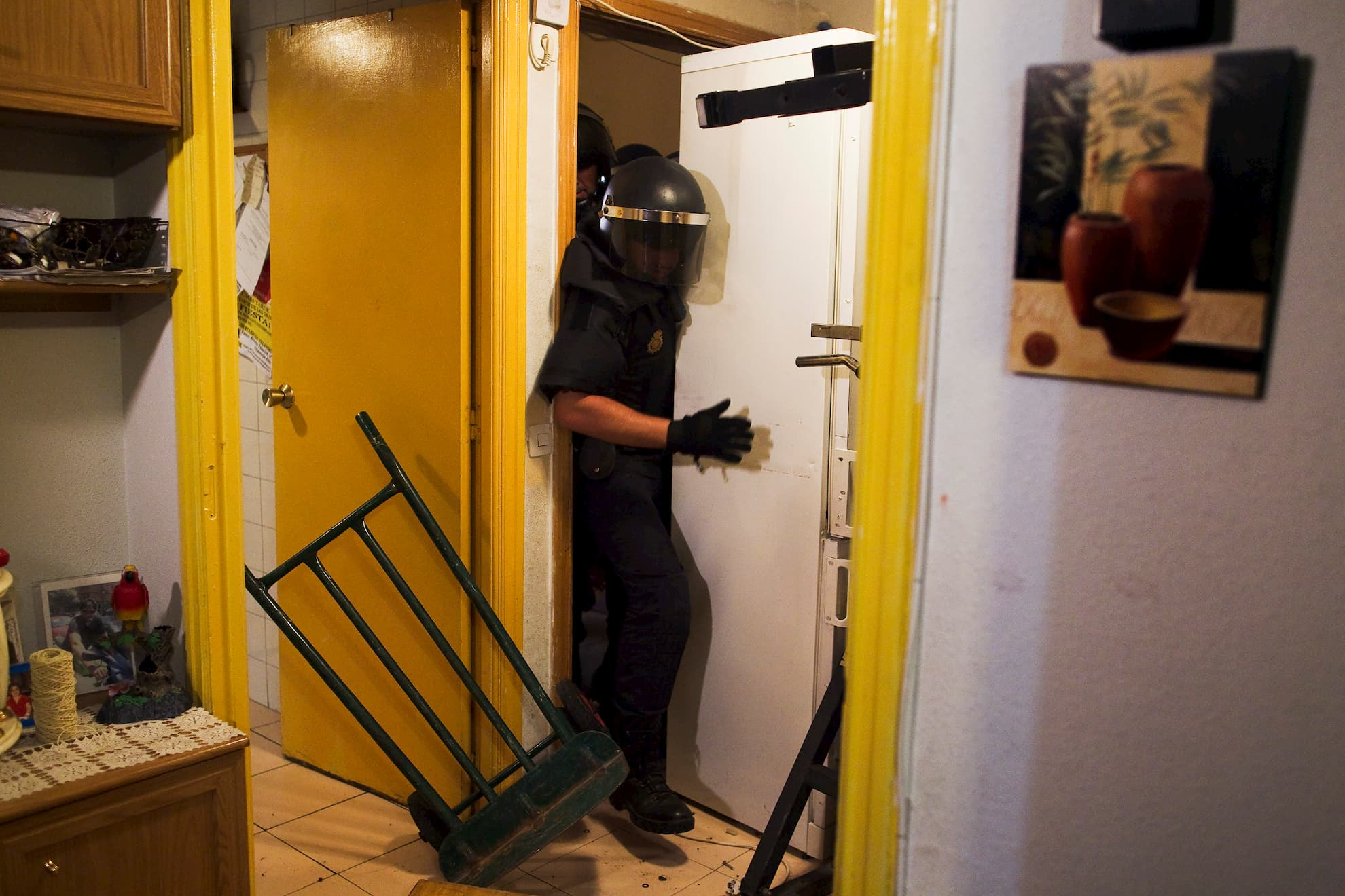 Police break into Maria Isabel Rodriguez Romero's apartment to evict her and her family in Madrid, Wednesday, Sept. 25, 2013. Romero, and six family members live in an apartment of the EMVS for 24 years and they had a debt of 1,200 euros.