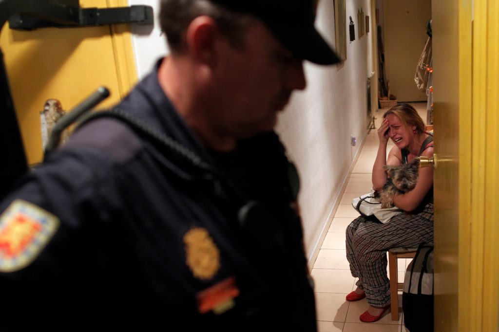 Maria Isabel Rodriguez Romero cries as police arrives to evict her and her family in Madrid, Wednesday, Sept. 25, 2013. Romero, and six family members live in an apartment of the EMVS for 24 years and they had a debt of 1,200 euros.