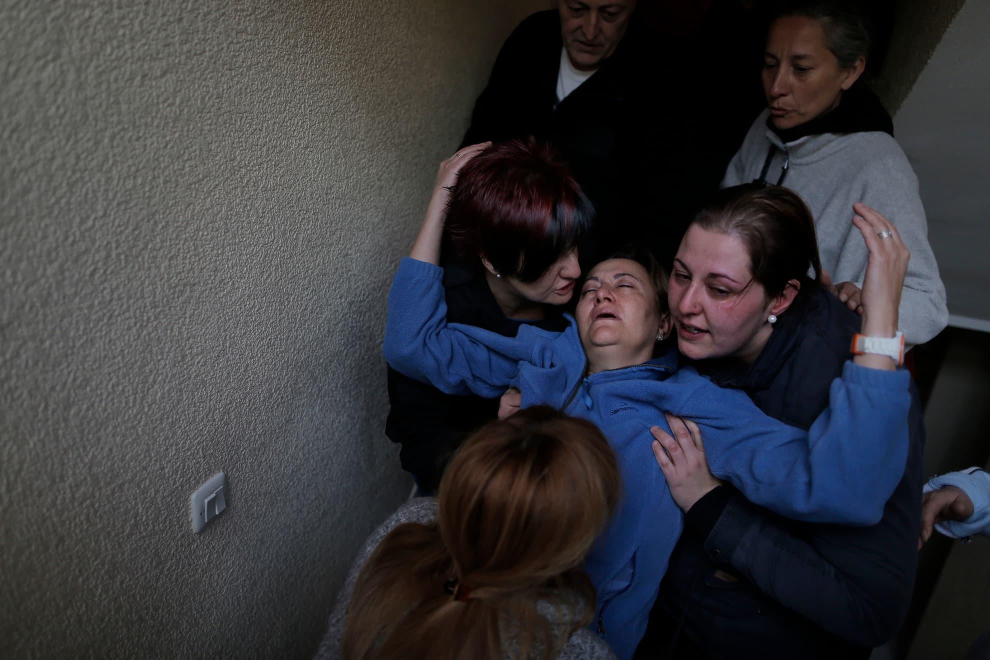 Soledad Carrasquilla Delgado, de 53 años, desempleada -en el centro de la imagen- recibe ayuda de su hija -a su derecha- y de su hermana, a su izquierda; su marido -en la parte superior izquierda- y dos miembros de la Plataforma de Afectados por la Hipoteca (PAH) -en la parte superior derecha e inferior de la foto- al desmayarse por un ataque de pánico después del aplazamiento de su desahucio y el de su familia en Madrid, el miércoles 30 de octubre de 2013.