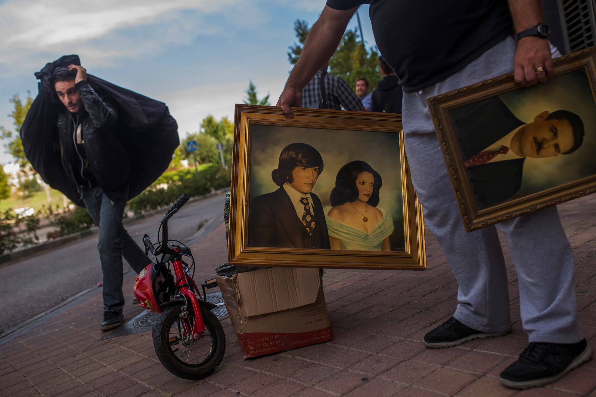 Friends an activists carry pictures and bags as they help Veronica Labradas to move out after the police evict her in Madrid, Wednesday, Oct. 22, 2014. Labradas, and her family occupied an apartment six months ago as they could not afford to pay their rent after loosing their business.