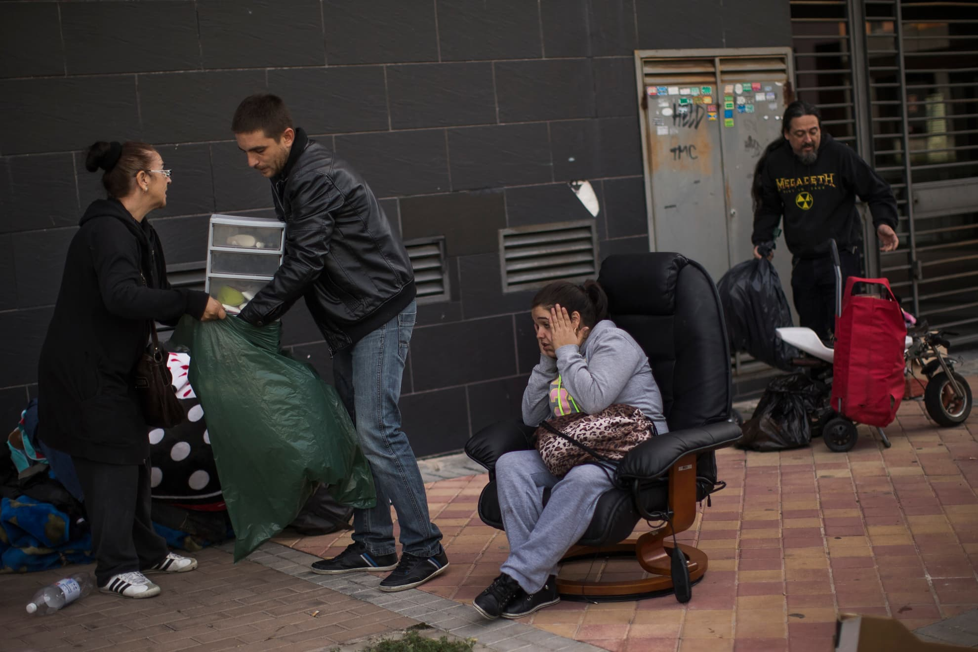 Veronica Labradas, center, stands outside her apartment with her belongings after the police evict her and her family in Madrid, Wednesday, Oct. 22, 2014. Labradas, and her family occupied an apartment six months ago as they could not afford to pay their rent after loosing their business.