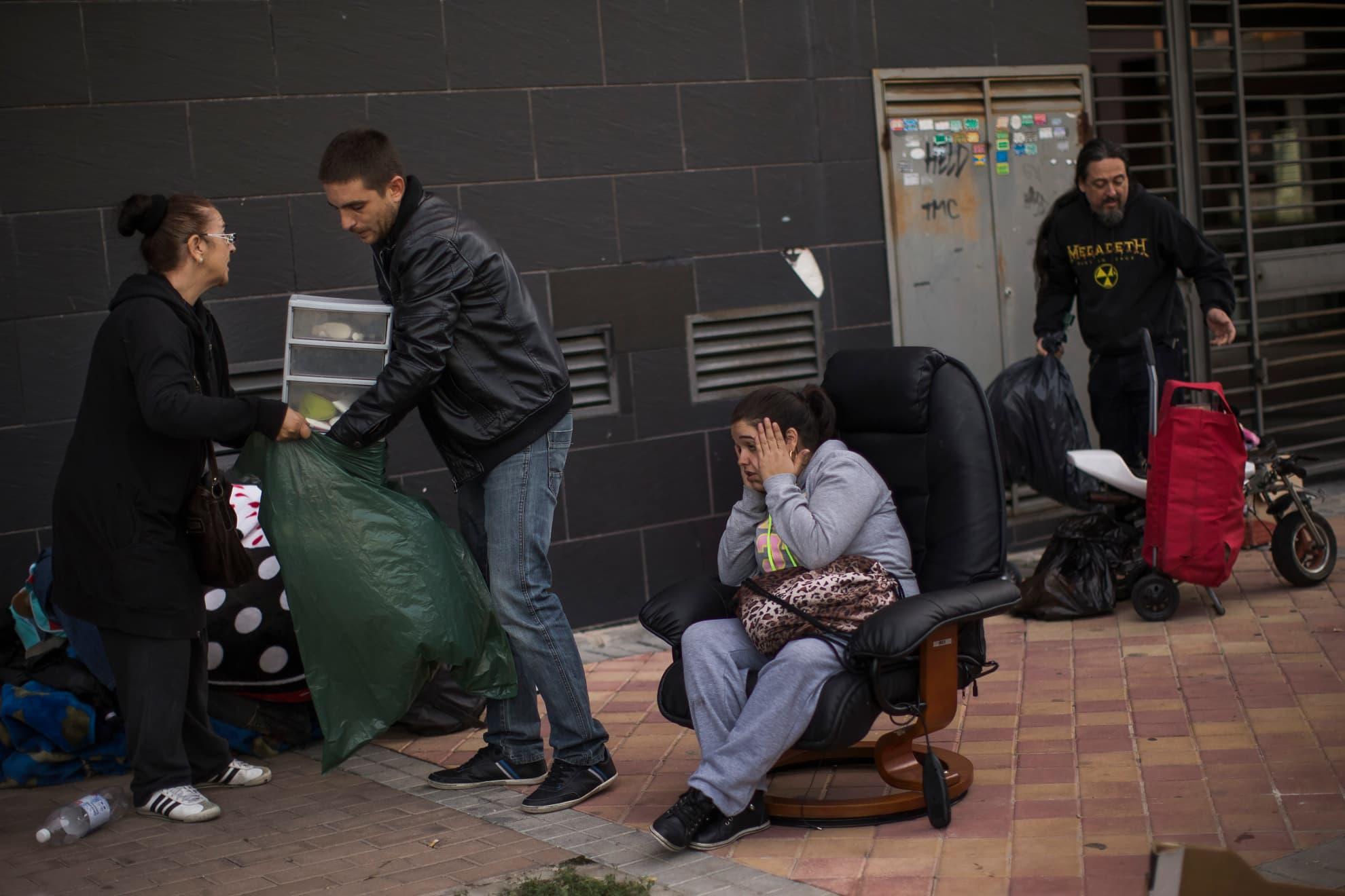 Verónica Labradas, en el centro de la imagen, permanece fuera de su vivienda con sus pertenencias tras haber sido desahuciada junto a su familia por la Policía en Madrid, el miércoles 22 de octubre de 2014. Labradas y su familia ocuparon un piso hace seis meses al no poder permitirse pagar un alquiler tras perder su negocio.