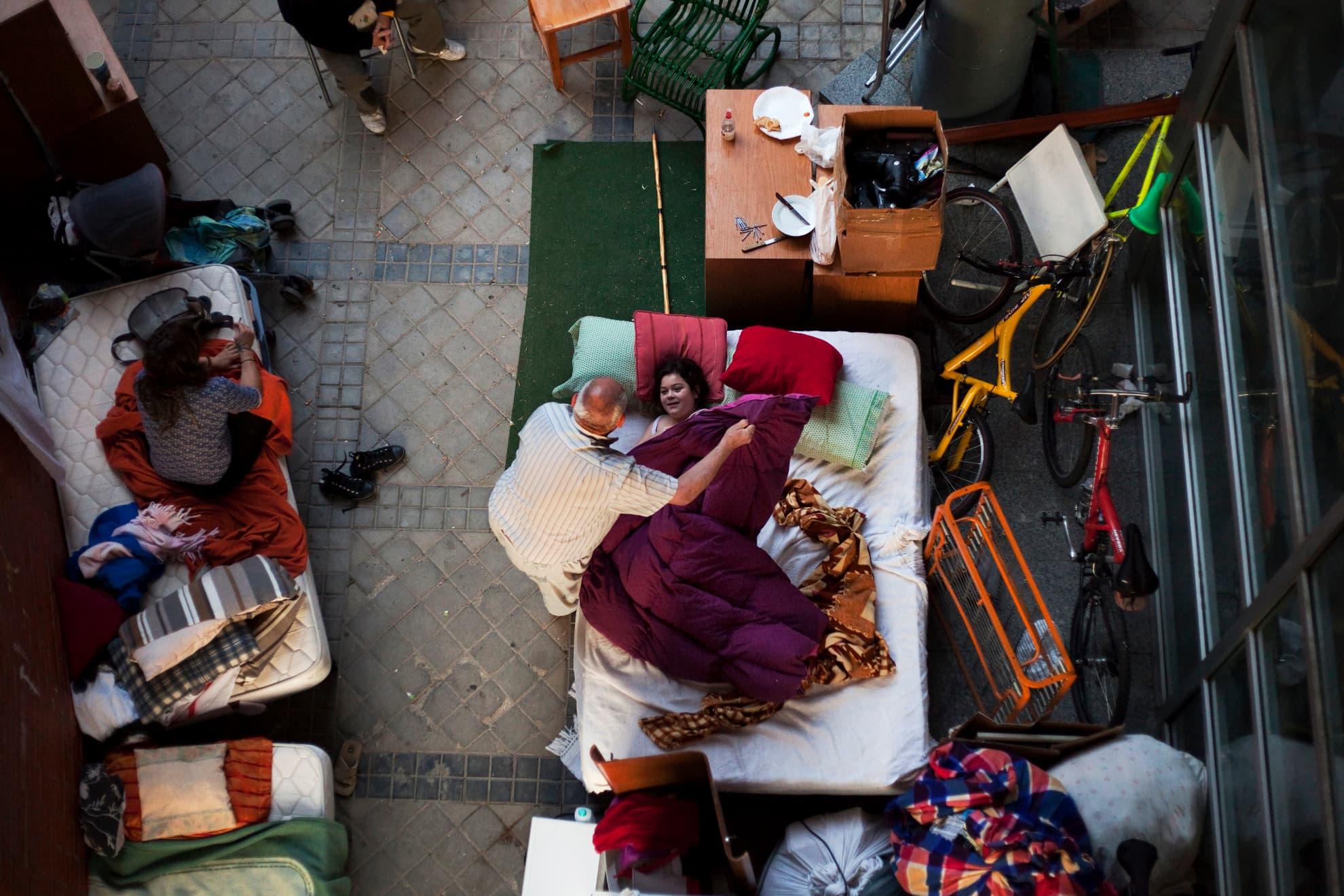 Efrén González, de 68 años, tapa a su nieta, que duerme en la calle tras haber sido desahuciados en Madrid el 26 de septiembre de 2013. Efrén Rodríguez González y los seis miembros de su familia vivieron en un piso de la EMVS (Empresa Municipal de la Vivienda y Suelo) durante 24 años y su deuda ascendía a 1.200 euros.