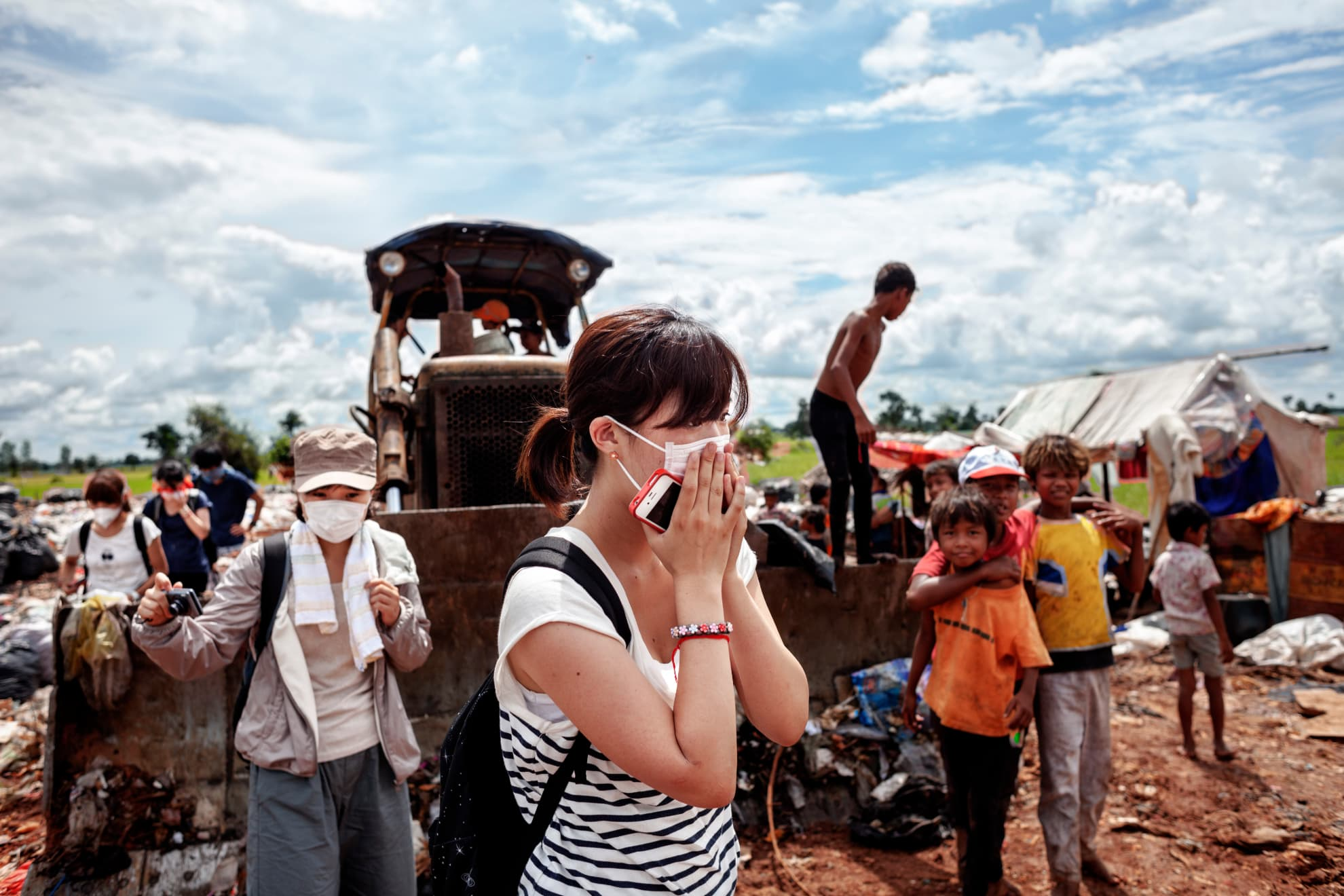 A Japanese tourist covers her mouth and nose from the foul smell given off by the gases at the Siem Reap rubbish dump (Cambodia). The visit there is part of a tourist route.