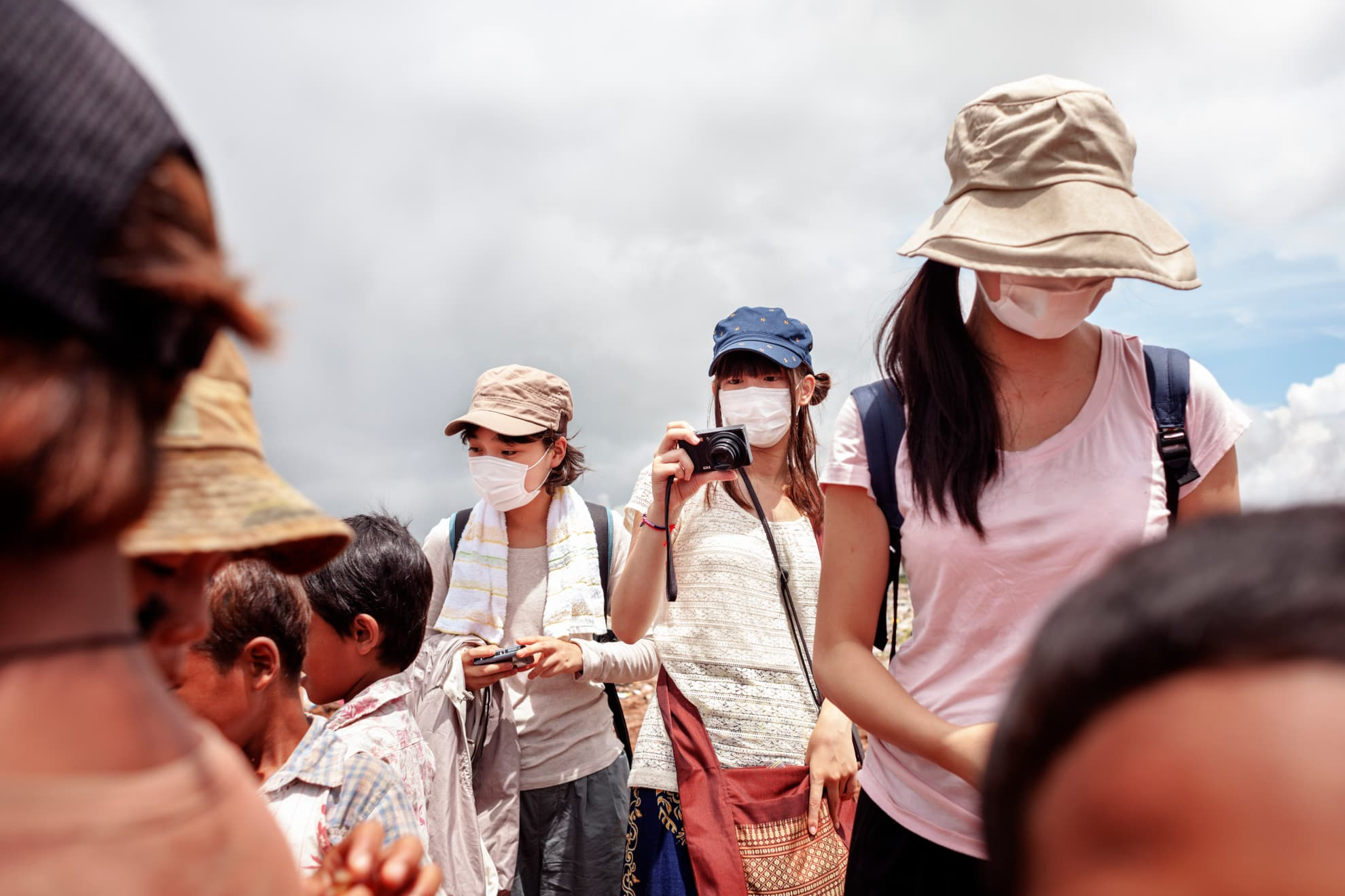 A Japanese tourist wearing a mask takes pictures of the children working in the rubbish dump. She is visiting the site as a tourist attraction.