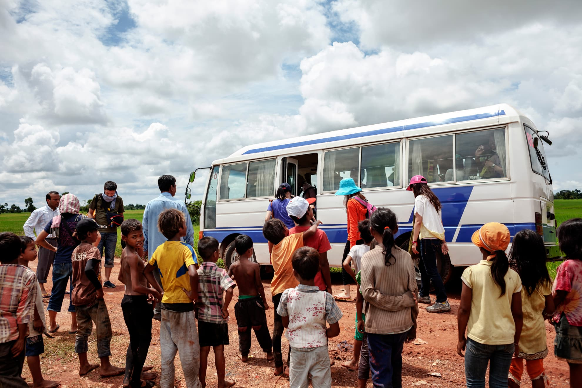 The tourist bus departs leaving behind the children whose pictures were taken and who were given candy. Korean, English and Japanese tourists normally visit Siem Reap rubbish dump in Cambodia.