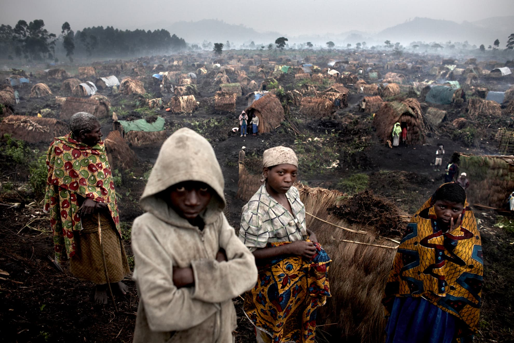 Internally displaced persons stand in the rain in the Chefferie IDP site, home to some 4,000 people, in the town of Kitchanga, North Kivu, DR Congo. The camp started to form in Oct/Nov 2007 and as of Feb 2008 still had not received humanitarian assistance due to the instability of the area.